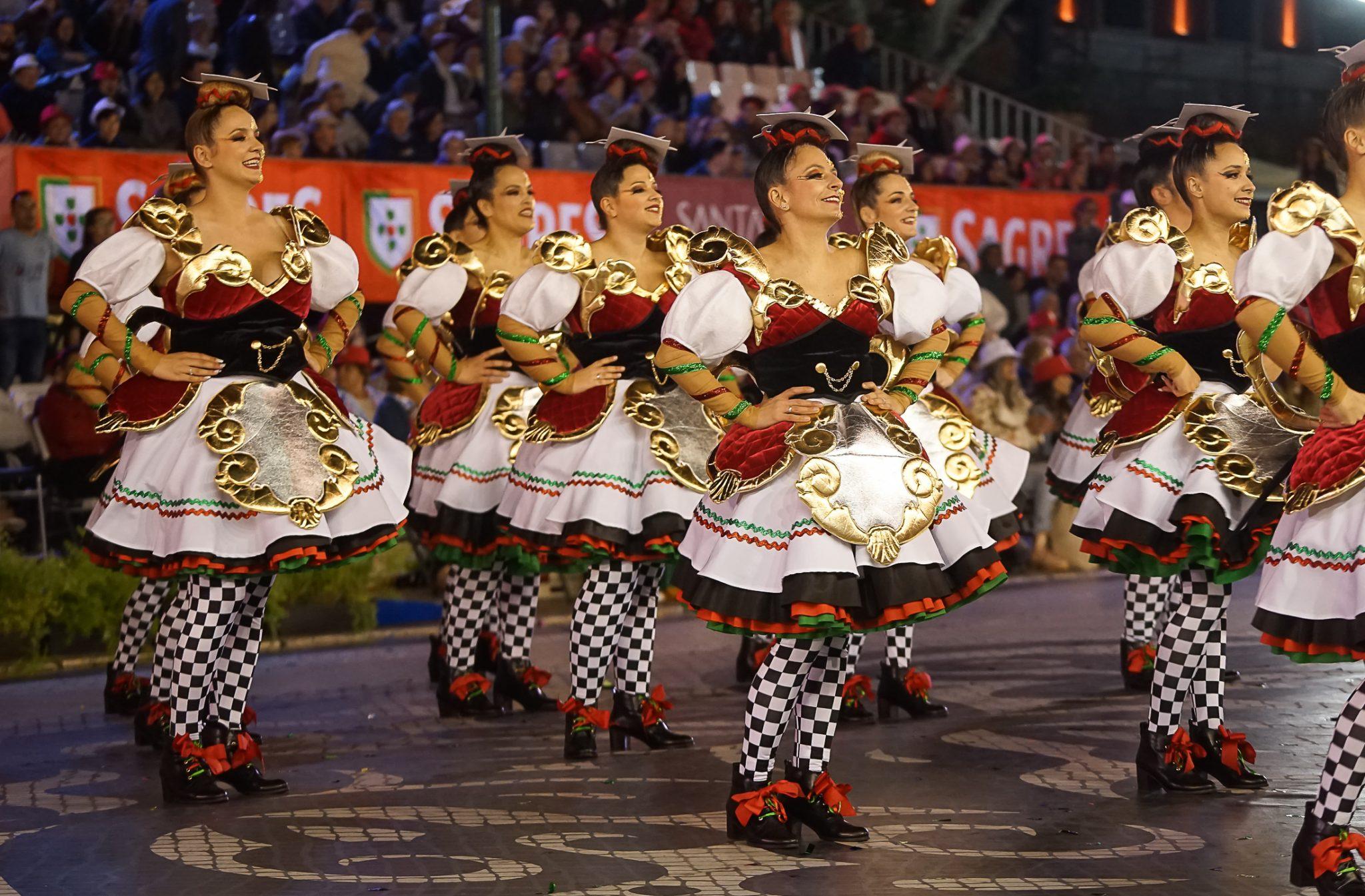 Mulheres, de lado para o observador, marcham com as mãos à cintura. Estão vestidas com uma saia rodada em branco e pormenores pretos, vermelhos, verdes e dourados.