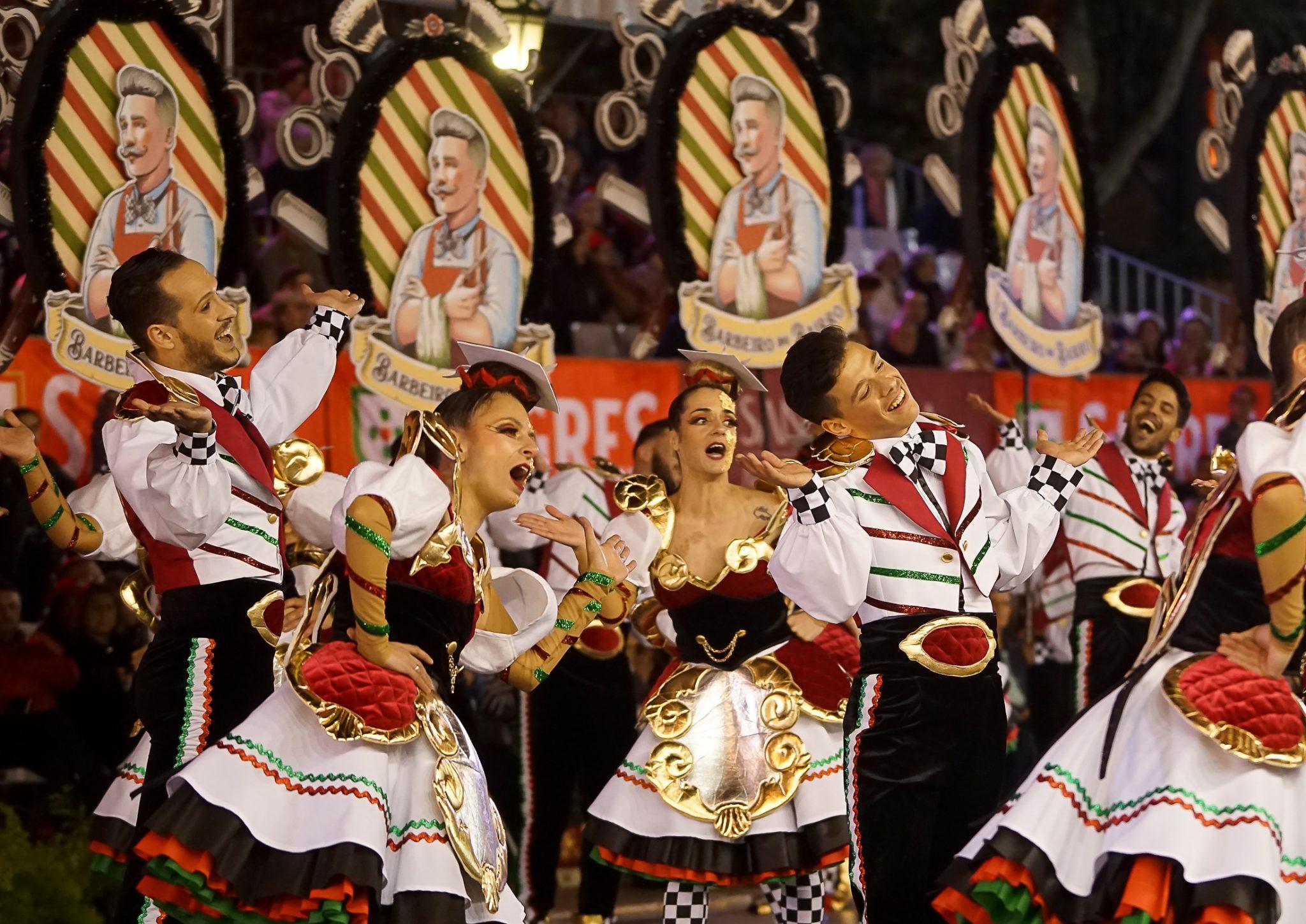 Homens e mulheres cantam e dançam vestidos com roupas pretas, brancas e vermelhas de lado para o observador. Atrás podem ver-se os arcos com uma figura desenhada de um barbeiro