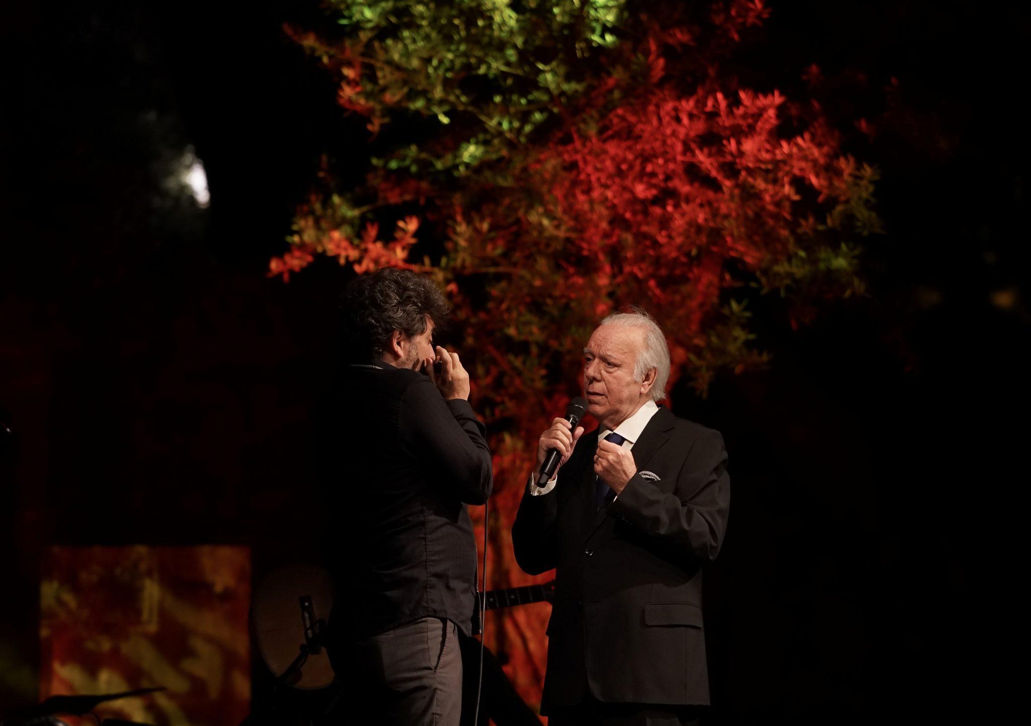 De lado para o observador, o fadista Carlos do Carmo frente a Antonio Serrano, que toca harmónica. Atrás de ambos, um fundo de árvores iluminadas em tons de verde e vermelho