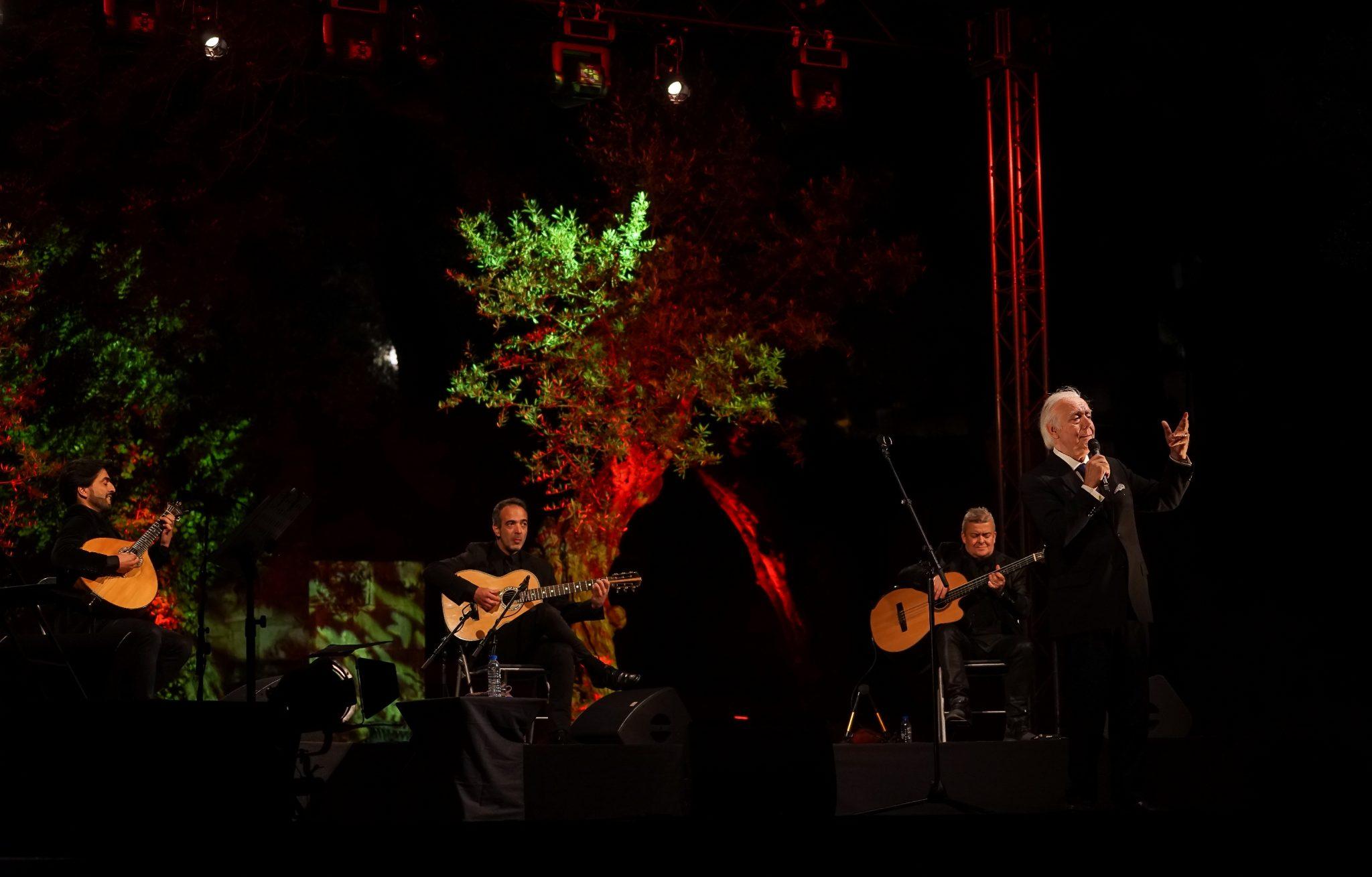 De lado para o observador, Carlos do Carmo canta de microfone na mão. Atrás do fadista, à esquerda do observador, os músicos.
