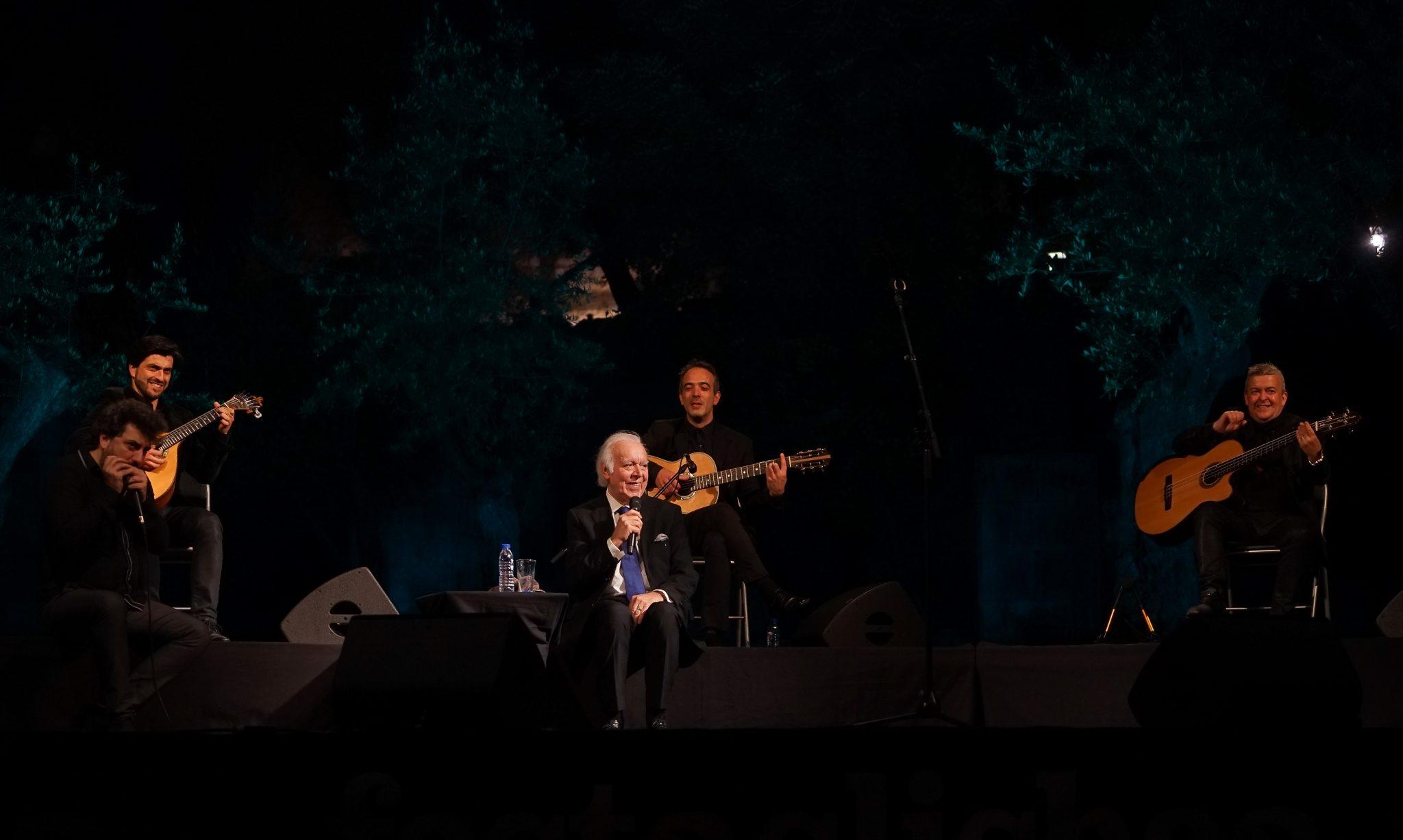 Vista do palco do concerto de Carlos do Carmo, com o fadista ao centro sentado numa cadeira, rodeado pelos músicos à esquerda e à direita.