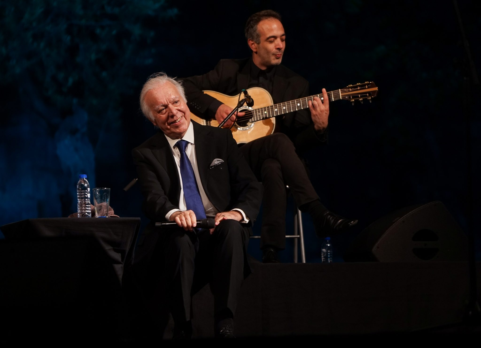 O fadista Carlos do Carmo sorri para o público, de frente para o observador, sentado no palco. Atrás do fadista o viola de fado.