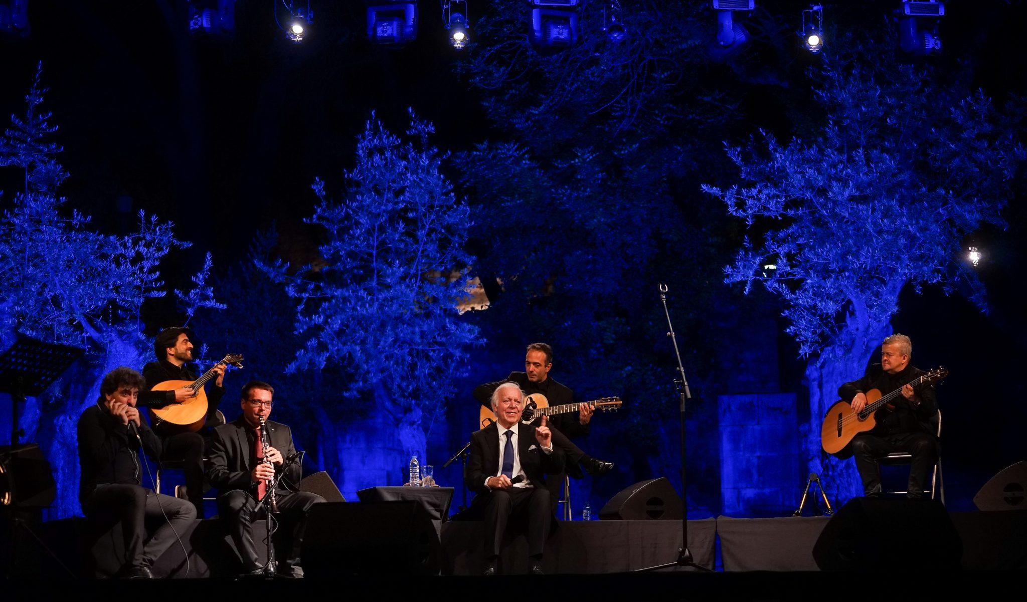Vista do palco do concerto de Carlos do Carmo, com o fadista ao centro sentado numa cadeira, rodeado pelos músicos à esquerda e à direita. Atrás vêem-se árvores iluminadas por luzes azuis.