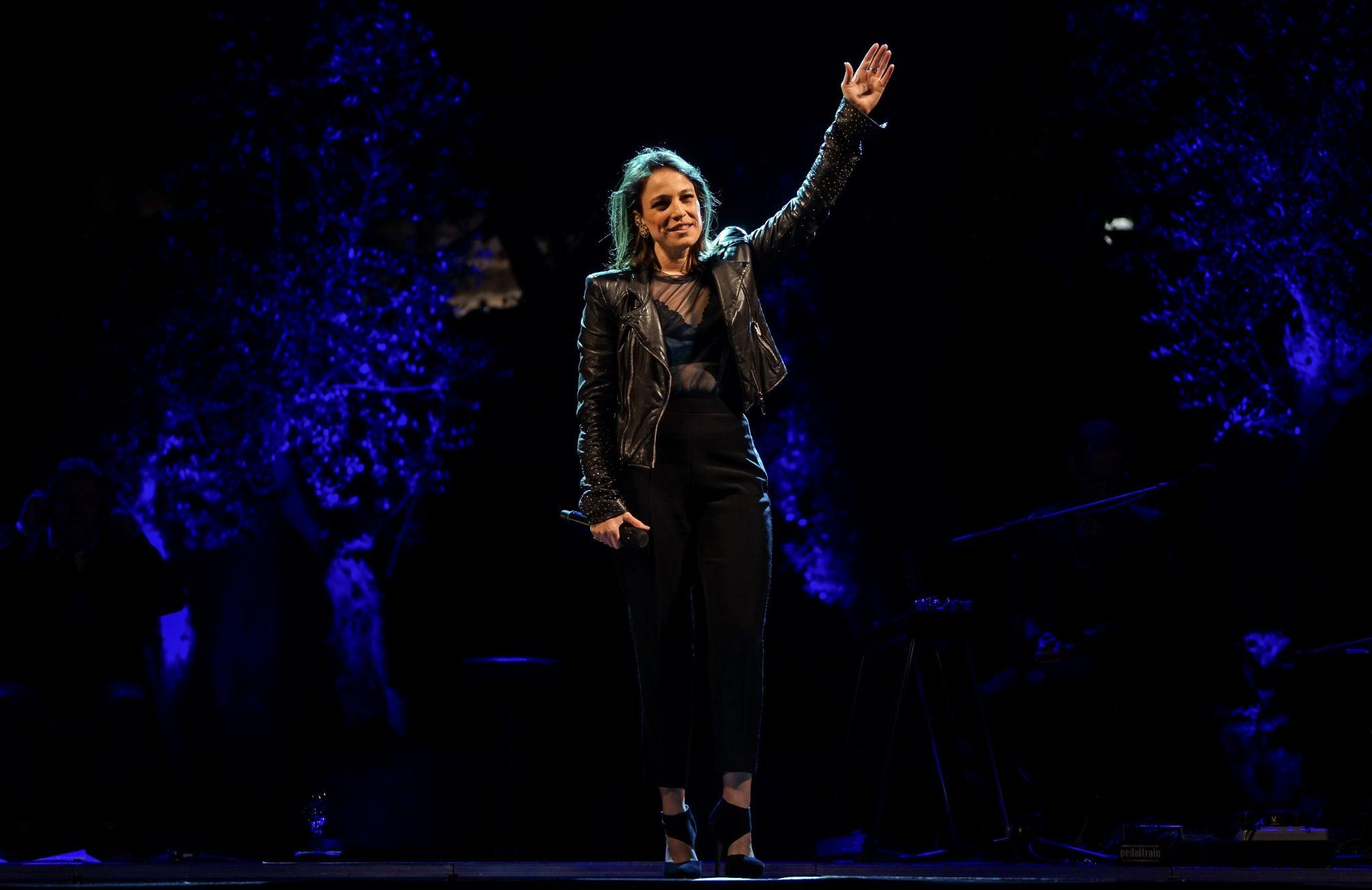 Carminho, em cima do palco, de braço no ar acenando ao público. A fadista está vestida de calças e casaco preto