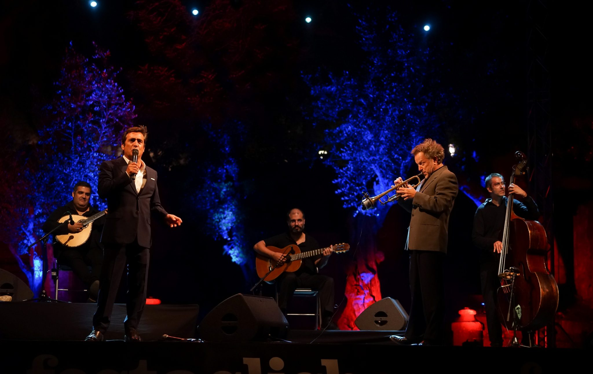 De frente para o observador, o fadista Camané canta em cima do palco. Do lado direito, o trompetista Laurent Filipe. Atrás o guitarrista, o violista e o contrabaixista.