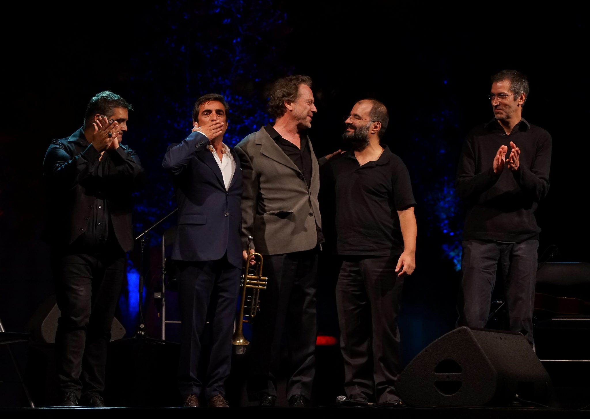 Camané e Laurent Filipe, rodeados pelos restantes músicos, agradecem os aplausos, abraçados no palco