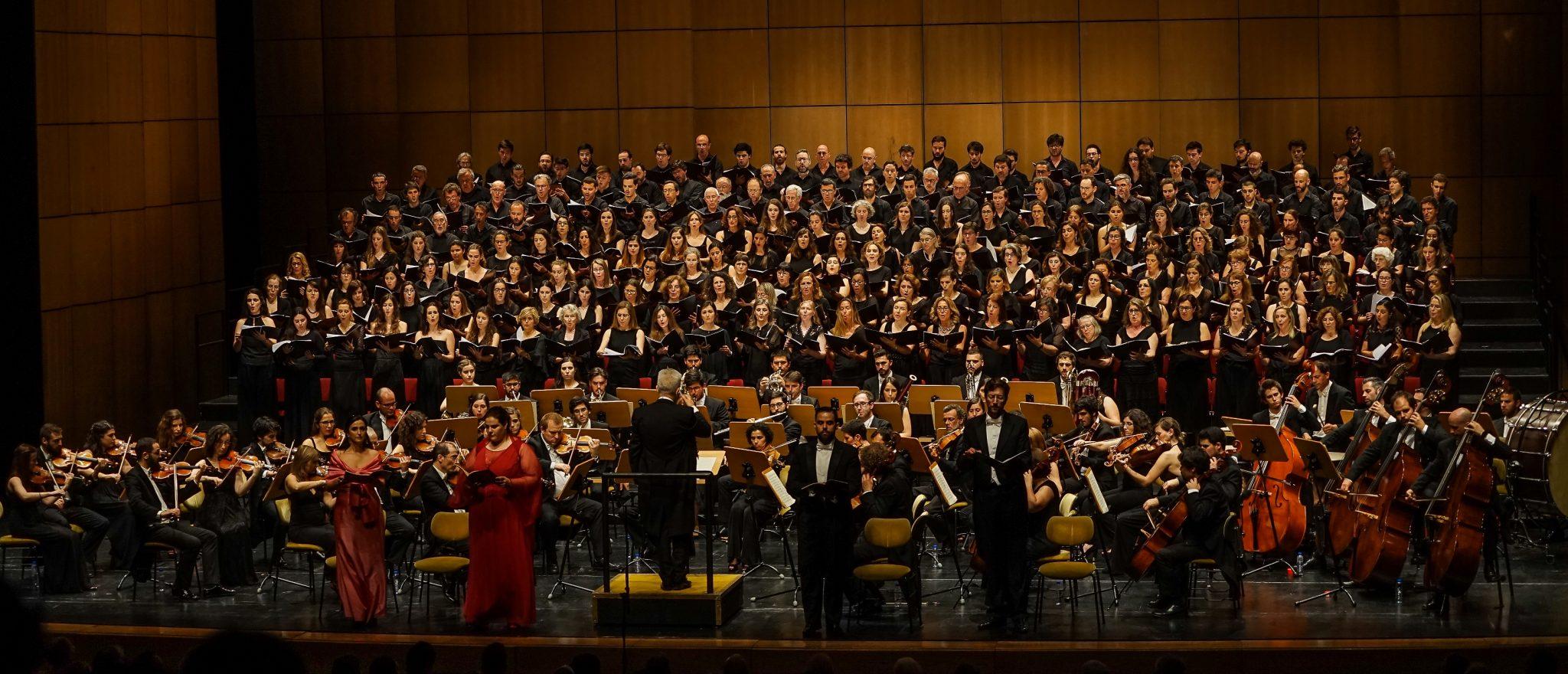 Visão do palco do Grande Auditório do Centro Cultural de Belém com coro, orquestra e quatro solistas de frente para o observador. As duas solistas, no lado esquerdo, estão vestidas de vermelho. Os dois solistas, no lado direito, estão de preto. Ao centro, e de costas para o observador, está o maestro.