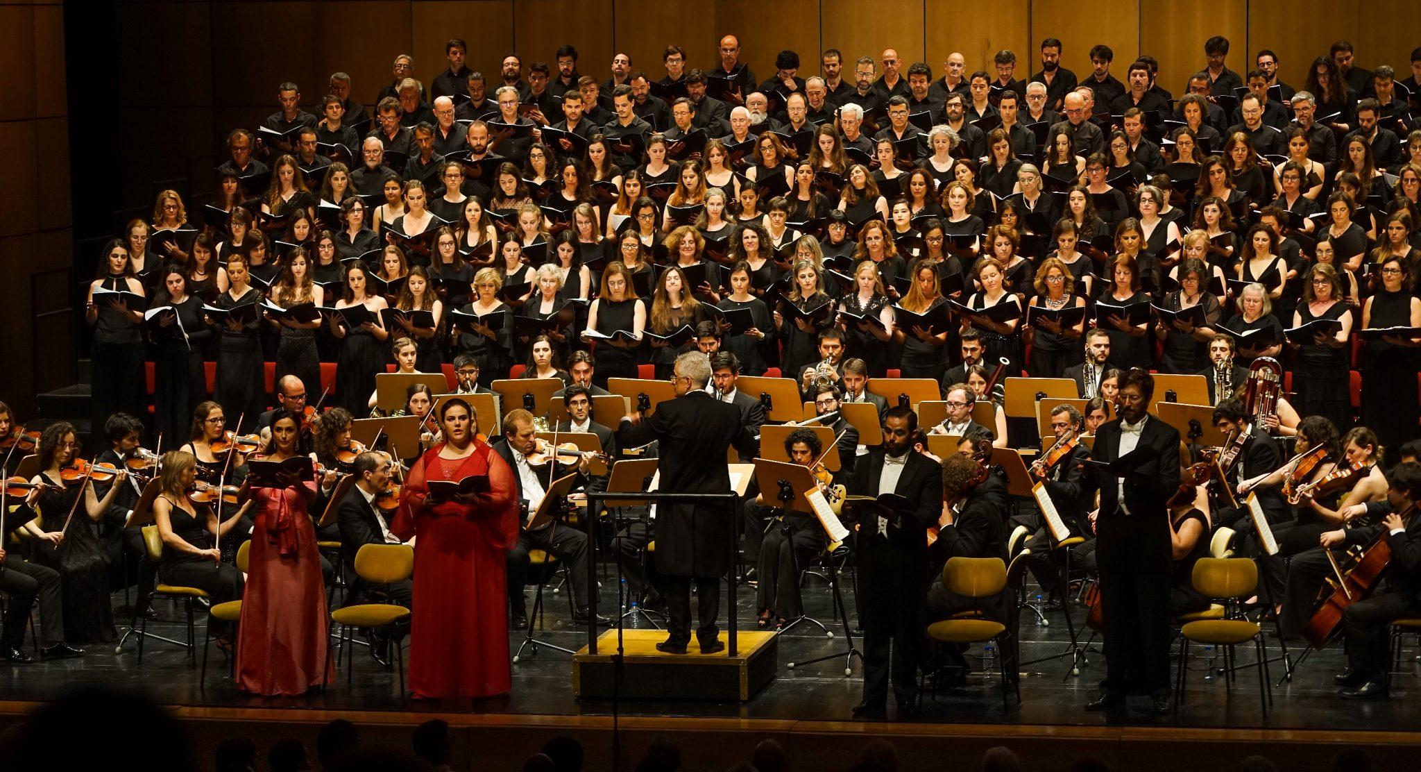 Palco do Grande Auditório do Centro Cultural de Belém com coro, orquestra e quatro solistas de frente para o observador. As duas solistas, no lado esquerdo, estão vestidas de vermelho. Os dois solistas, no lado direito, estão de preto. Ao centro, e de costas para o observador, está o maestro.