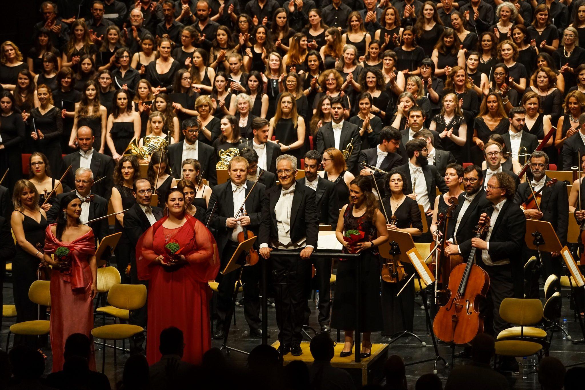 De frente para o observador, os participantes do concerto, incluindo coro, orquestra, maestro e solistas, encaram as palmas do público.