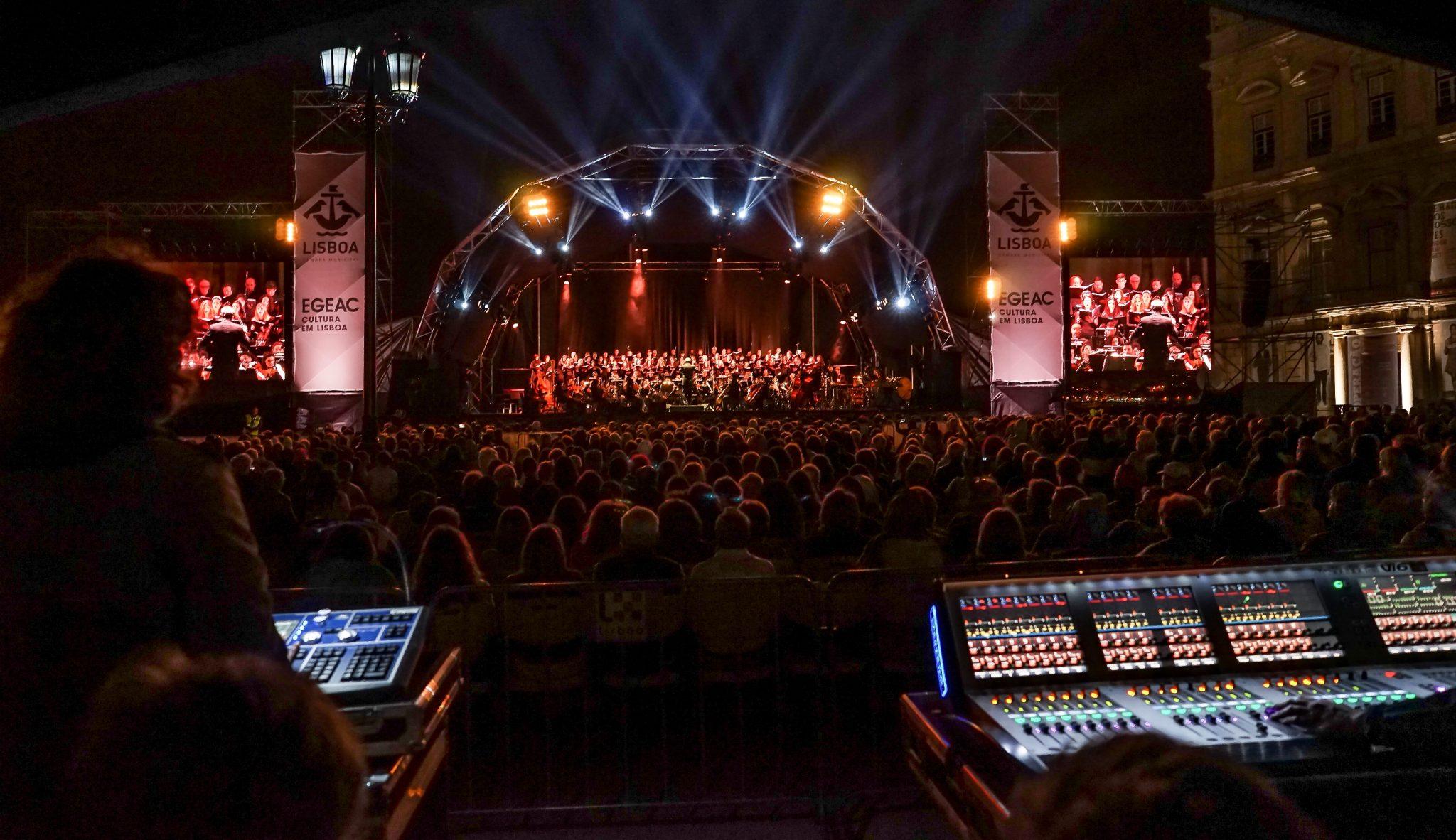Visão noturna do palco de um concerto e plateia repleta de pessoas, de frente para o observador, ladeados à direita pelo Torreão Poente da Praça do Comércio e com a mesa de som em primeiro plano.
