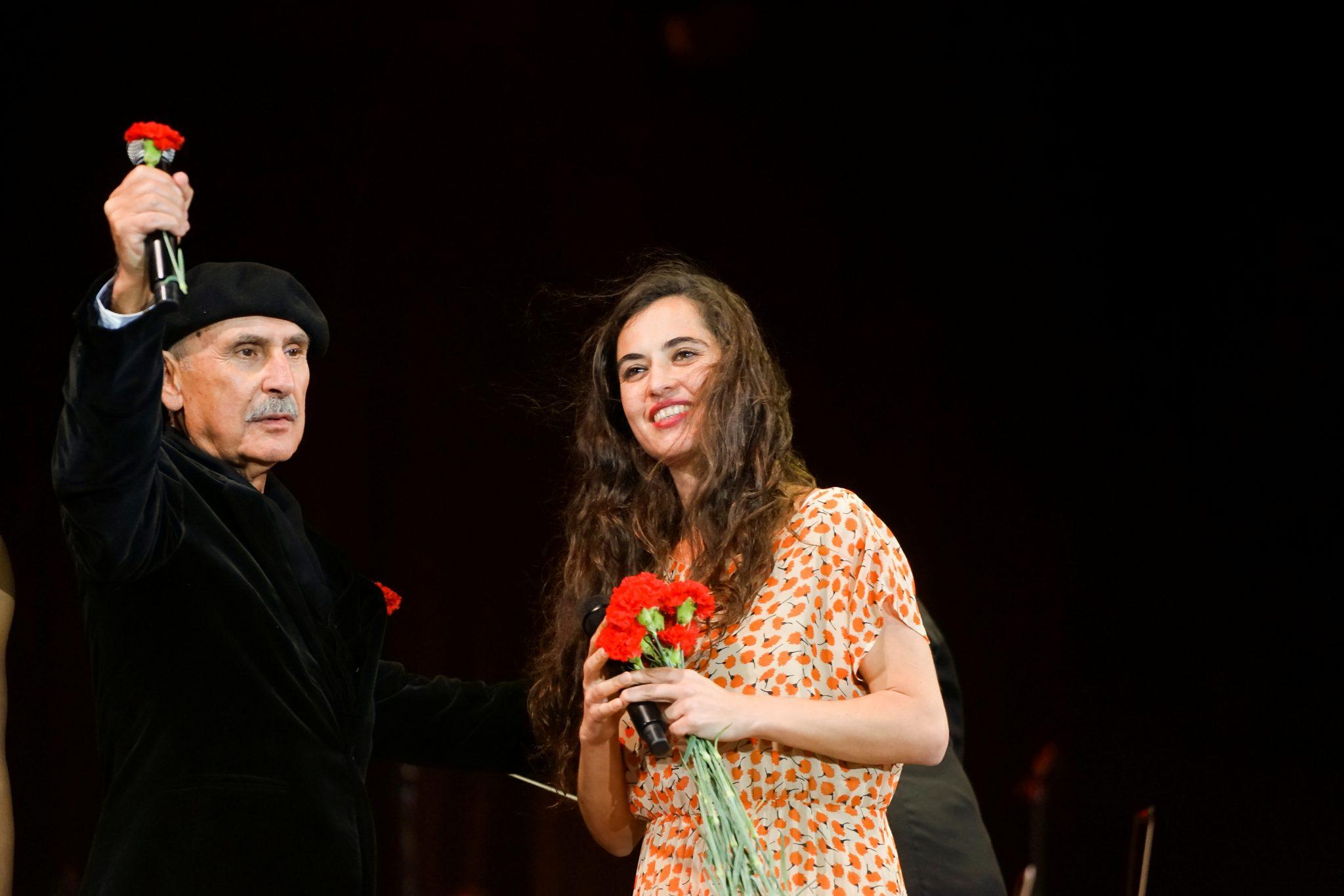 Plano médio de dois artistas, os cantores António Vitorino e Sílvia Perez Cruz, sob um fundo preto, empunhando cravos vermelhos.