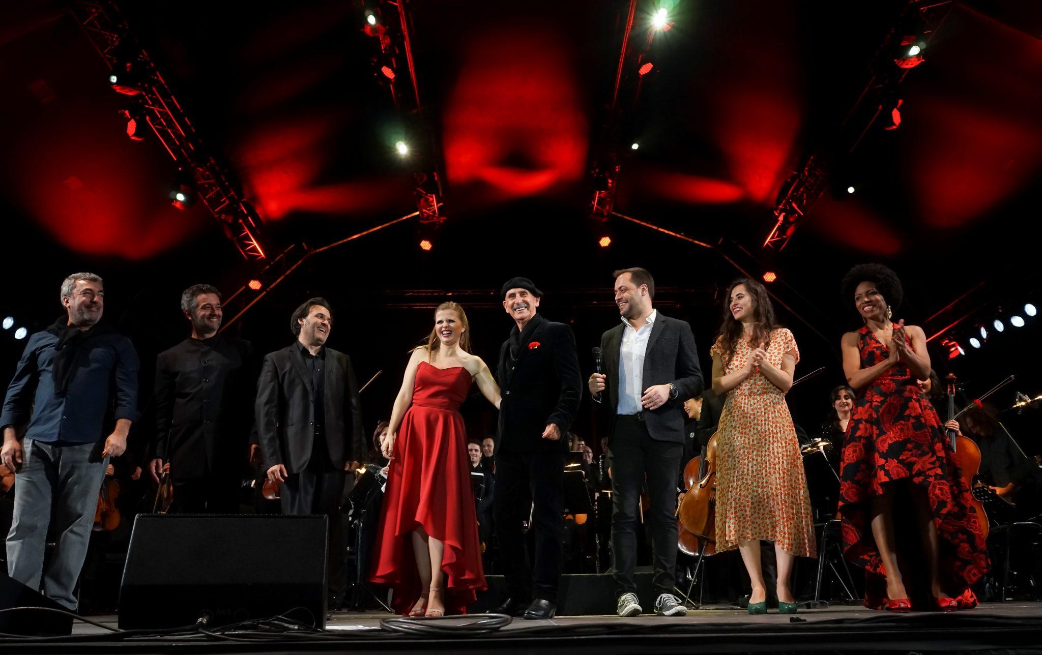 Em tons de preto e vermelho, a imagem de 8 músicos sorridentes, alguns batendo palmas, em palco.