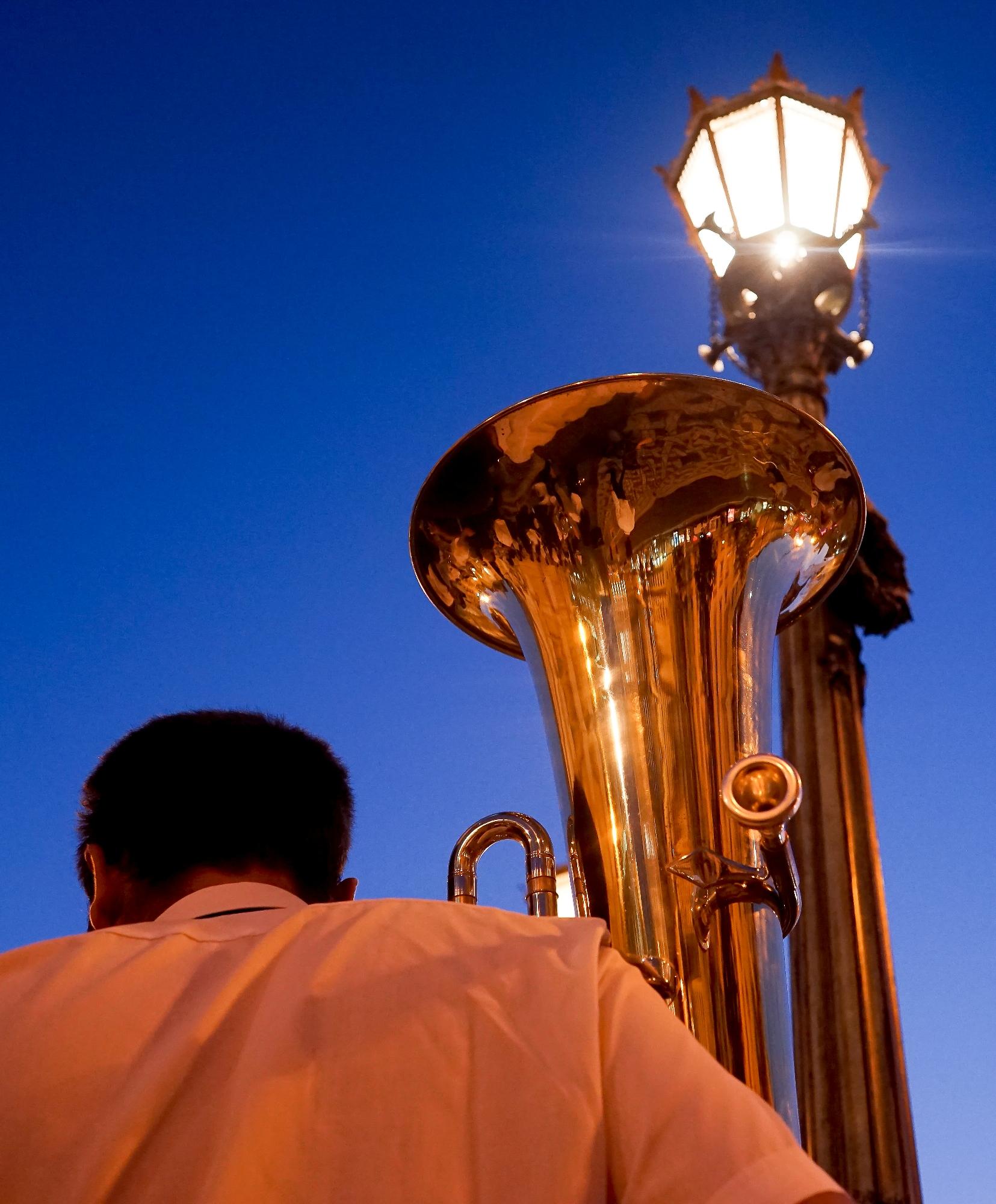 Pormenor de uma tuba e das costas de um músico. Em segundo plano, um candeeiro de iluminação pública aceso.