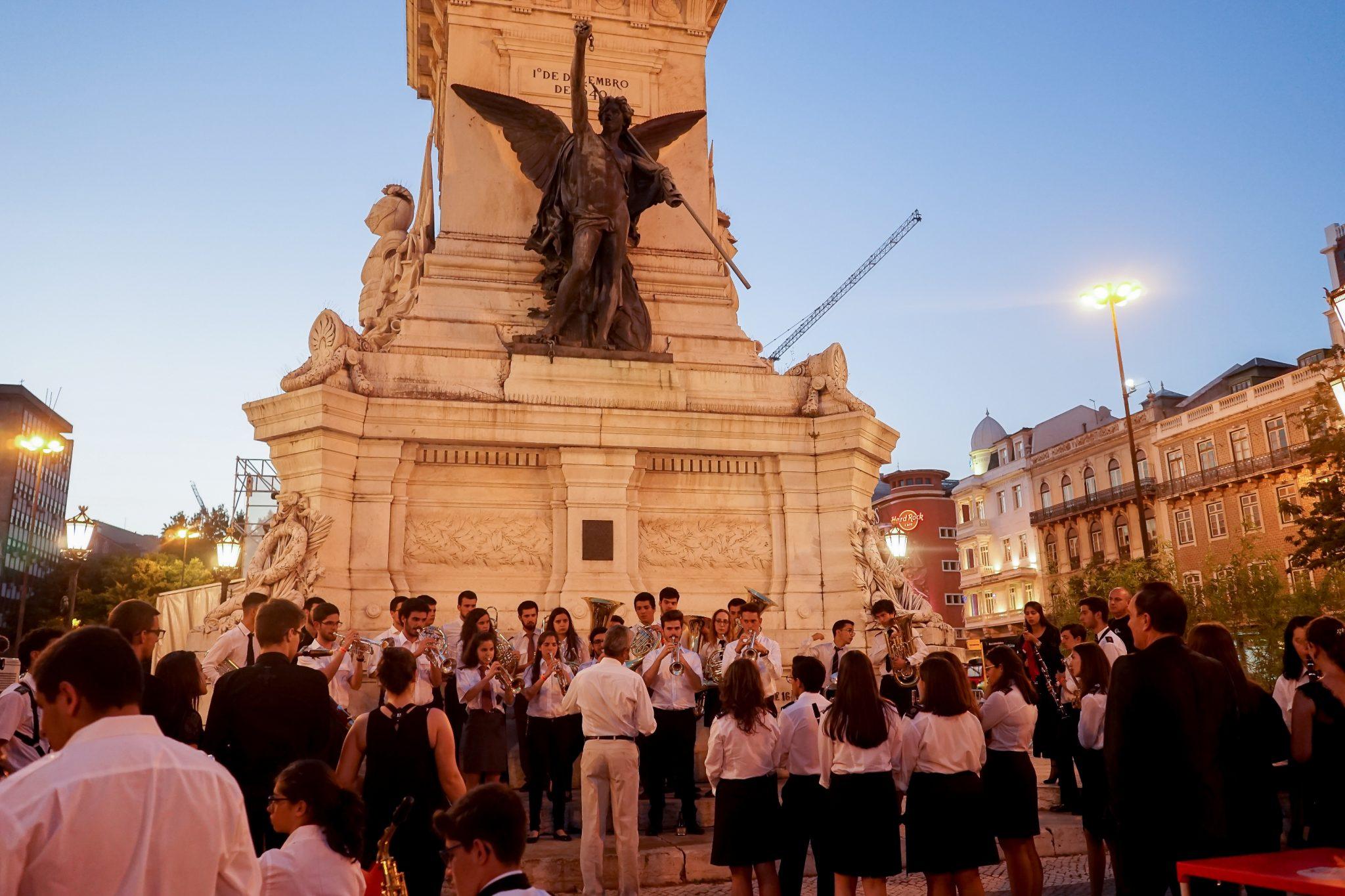 Um grupo de músicos afina os instrumentos sob o monumento da Praça dos Restauradores, do qual se destaca uma figura alada em bronze. Luz de fim de dia.