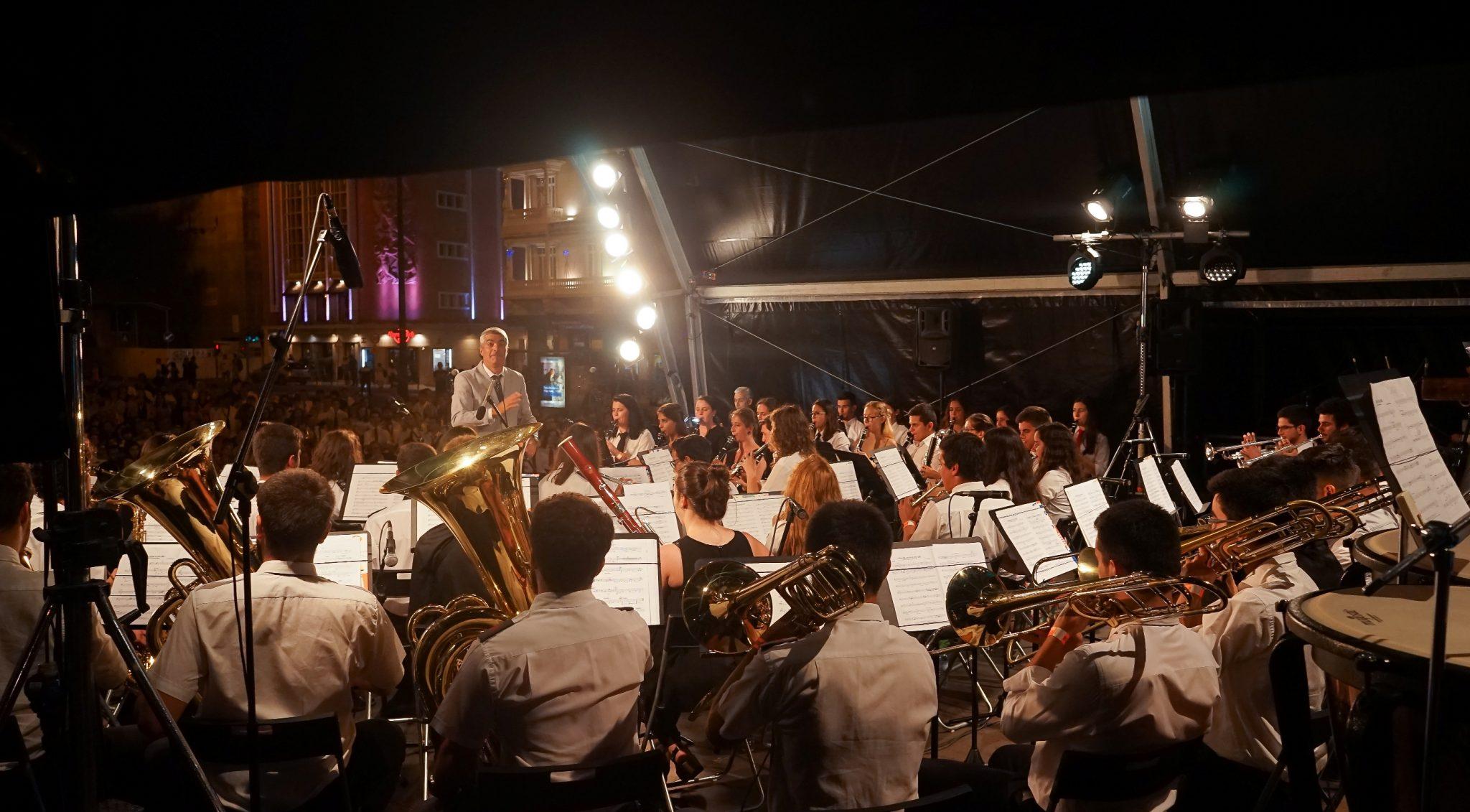 Vista do concerto da banda filarmónica a partir do interior do palco. De frente para o observador, o maestro de casaco cinza dirige os músicos.