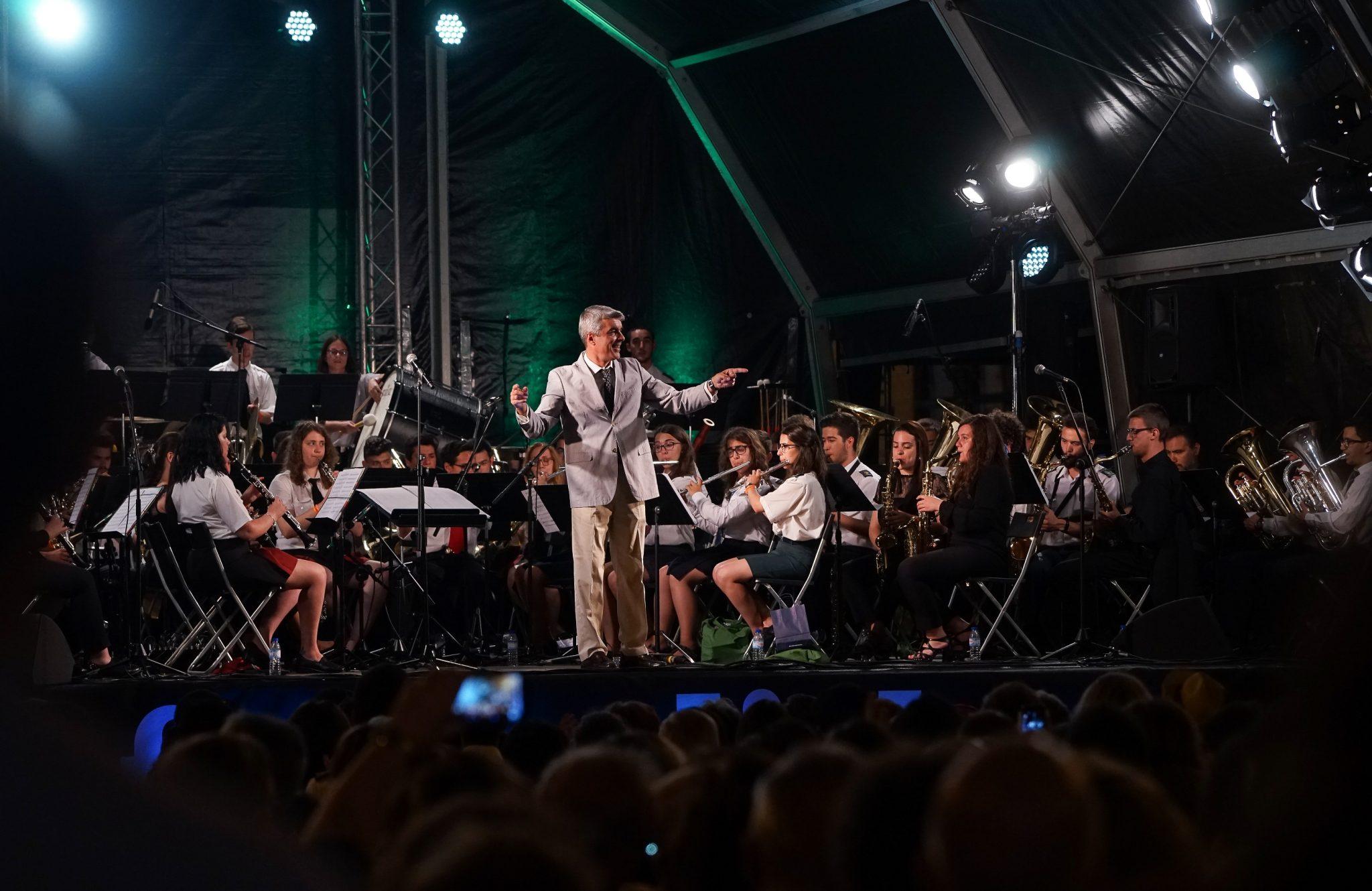 Banda filarmónica atua num palco de fundo preto. Ao centro, o maestro sorri para o público.