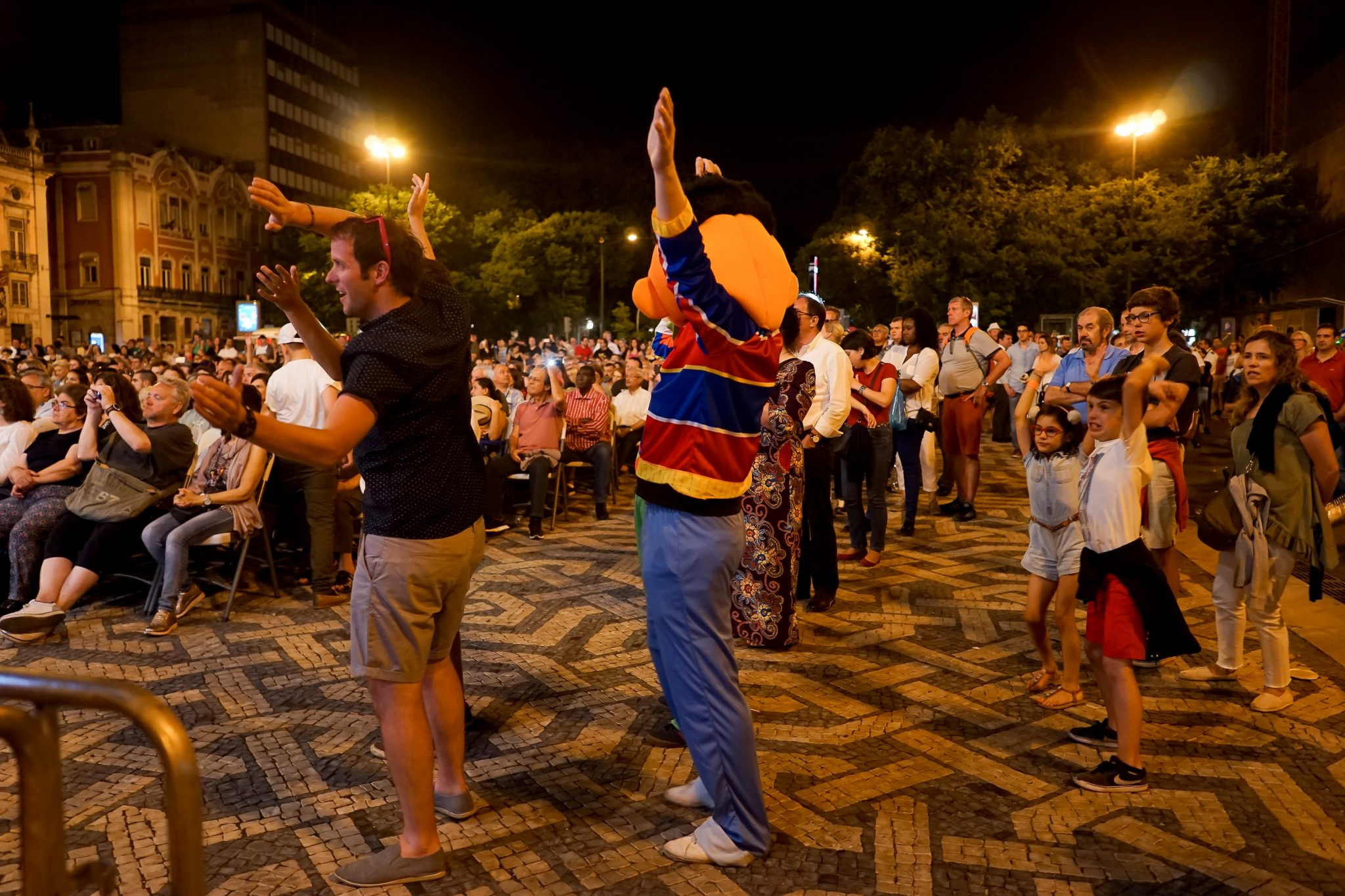 De lado para o observador, alguns espetadores de várias idades ondulam os braços no ar ao ritmo da música. Ao centro, um dos espetadores está vestido de Egas, personagem da Rua Sésamo. O concerto acontece na Praça dos Restaurados à noite.