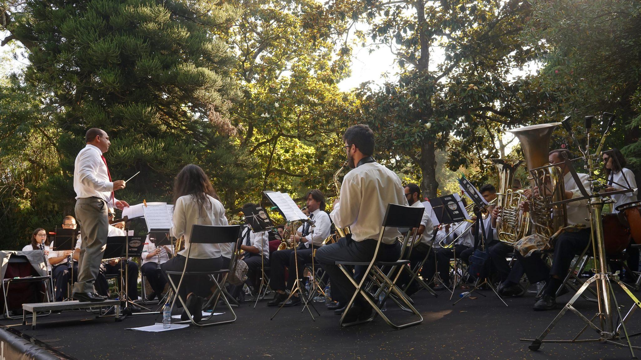 De lado para o observador, elementos de uma banda filarmónica atuam num jardim de árvores altas. No lado esquerdo, o maestro é o único elemento em pé na fotografia.