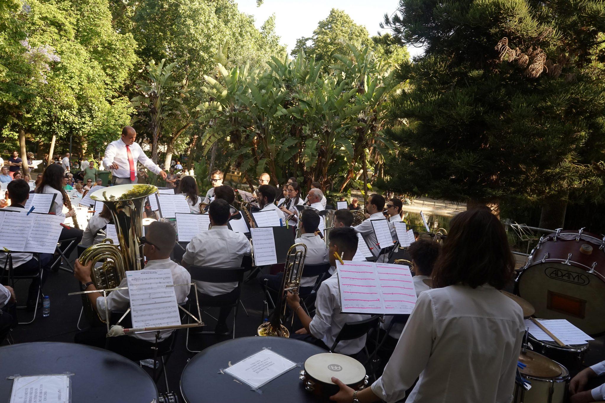 De costas para o observador, uma banda filarmónica, com todos os seus elementos sentados, atua no cenário de um jardim de árvores frondosas e verdejantes.