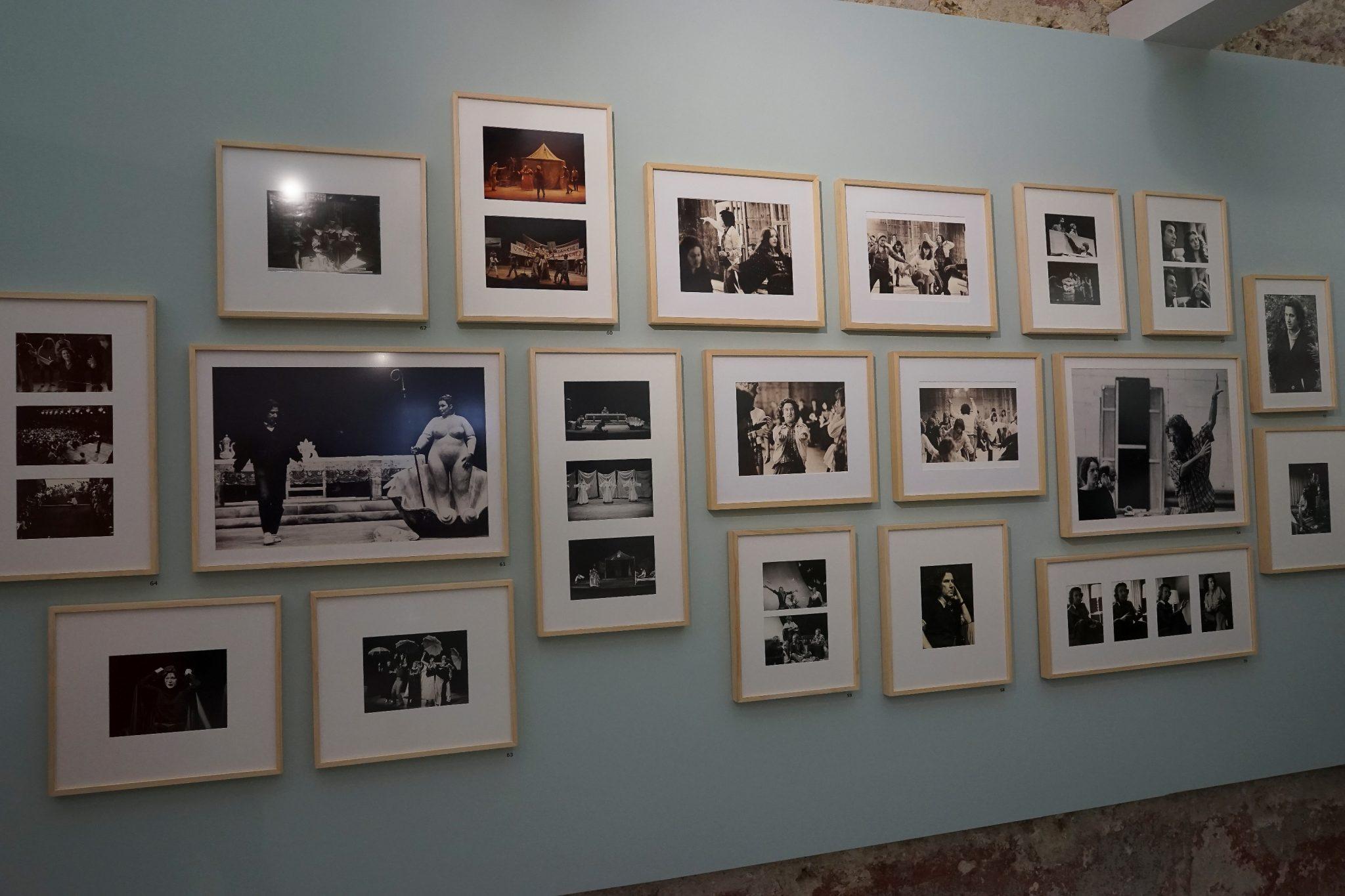 De frente para o observador uma parede, azul claro, exibindo várias fotografias emolduradas, a preto e branco e a cores.