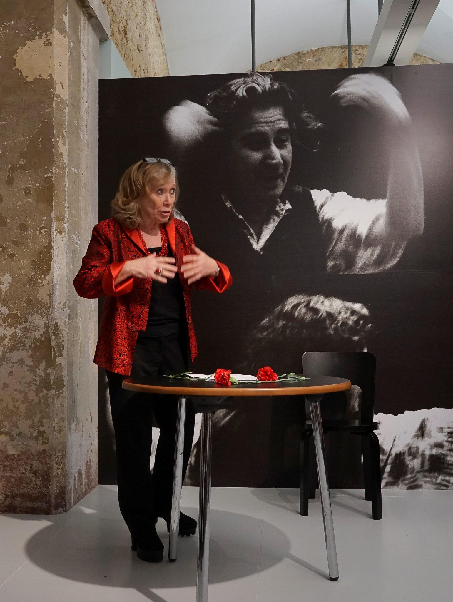 Vestida de vermelho e preto, em pé, do lado esquerdo e de frente para o observador, a atriz Maria do Céu Guerra gesticula junto a uma mesa onde estão pousados dois cravos vermelhos, contrastando com a fotografia a preto e branco, atrás de si, representando uma mulher de braços no ar.