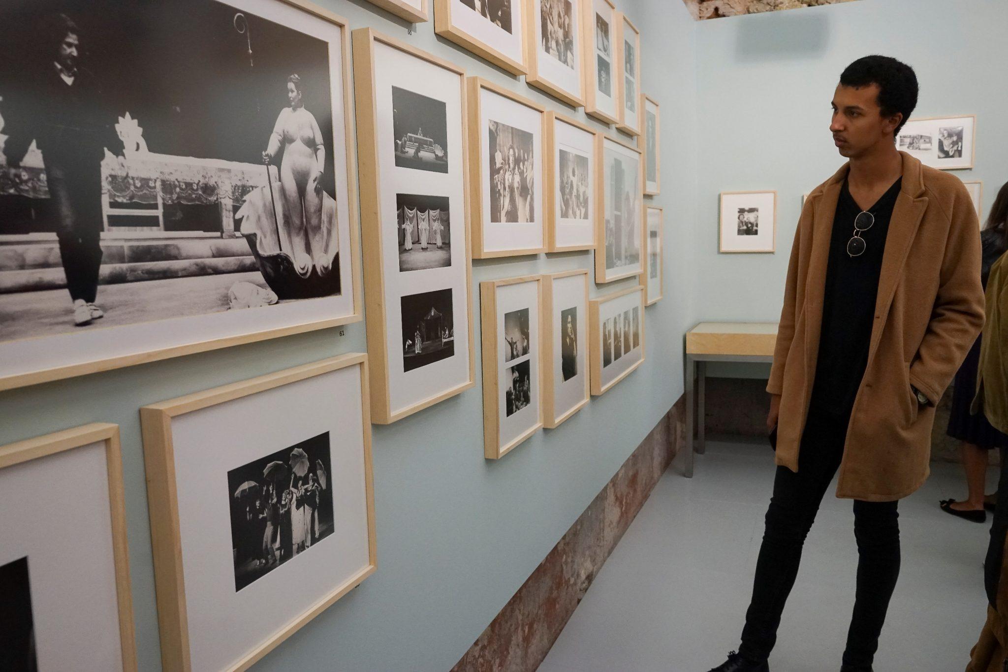 Lateral para o observador, uma parede preenchida de fotografias emolduradas de fotografias a preto e branco da exposição