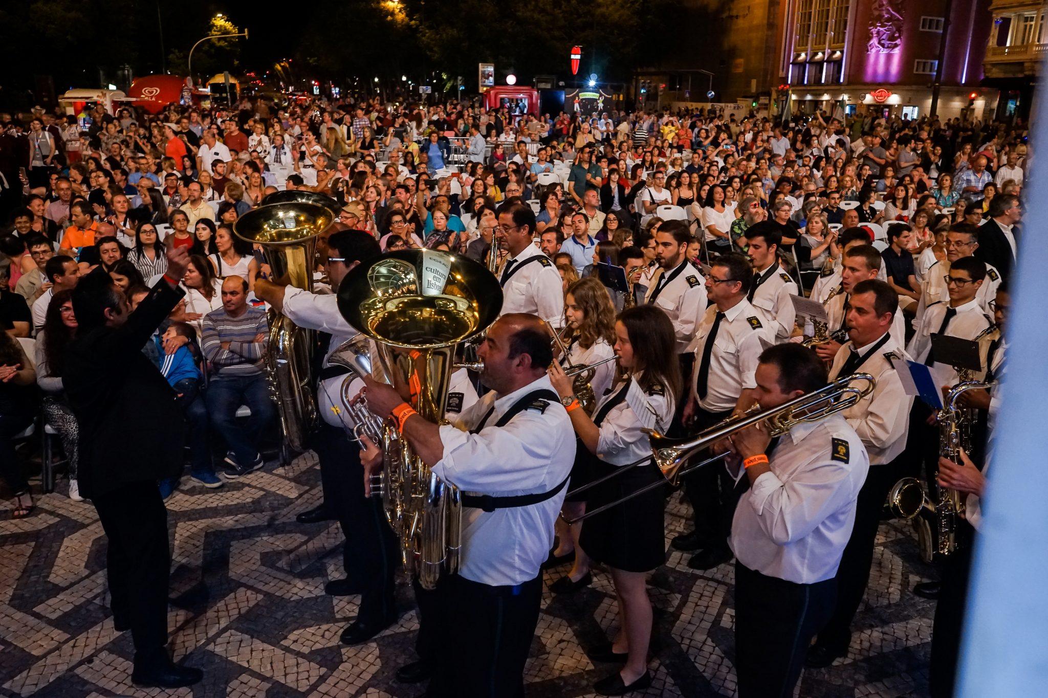 Em primeiro plano, e de lado para o observador, vários elementos de uma banda filarmónica, com camisas brancas, tocam instrumentos de sopro. Em segundo plano, centenas de pessoas sentadas assistem à atuação