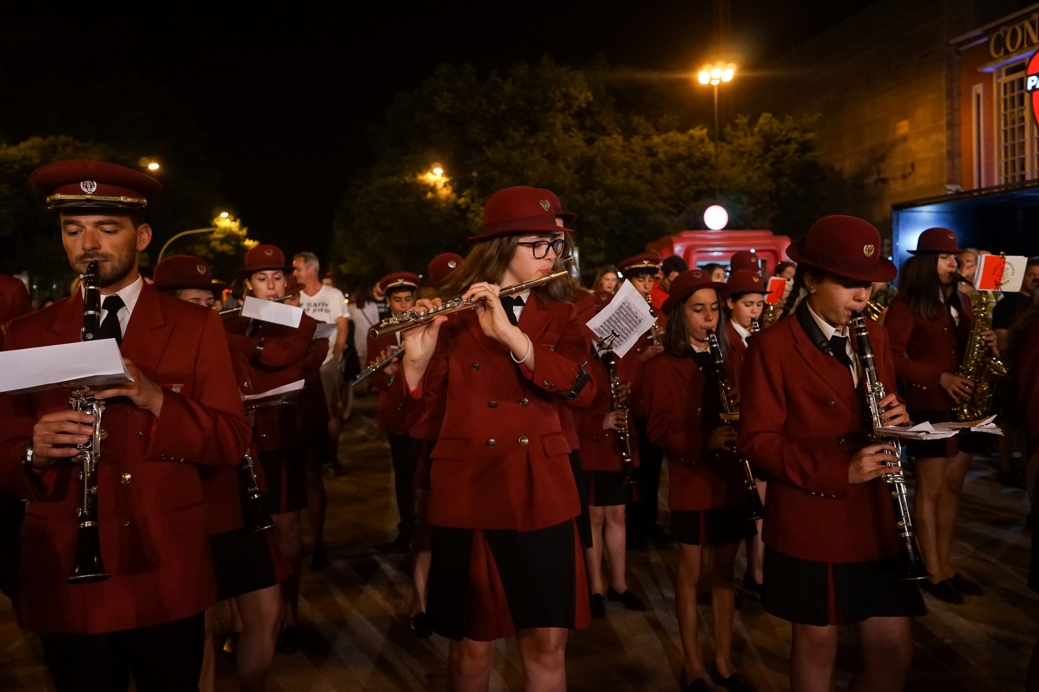 De frente para o observador, elementos de uma banda filarmónica com farda vermelha escura tocam instrumentos de sopro à noite na Praça dos Restauradores.