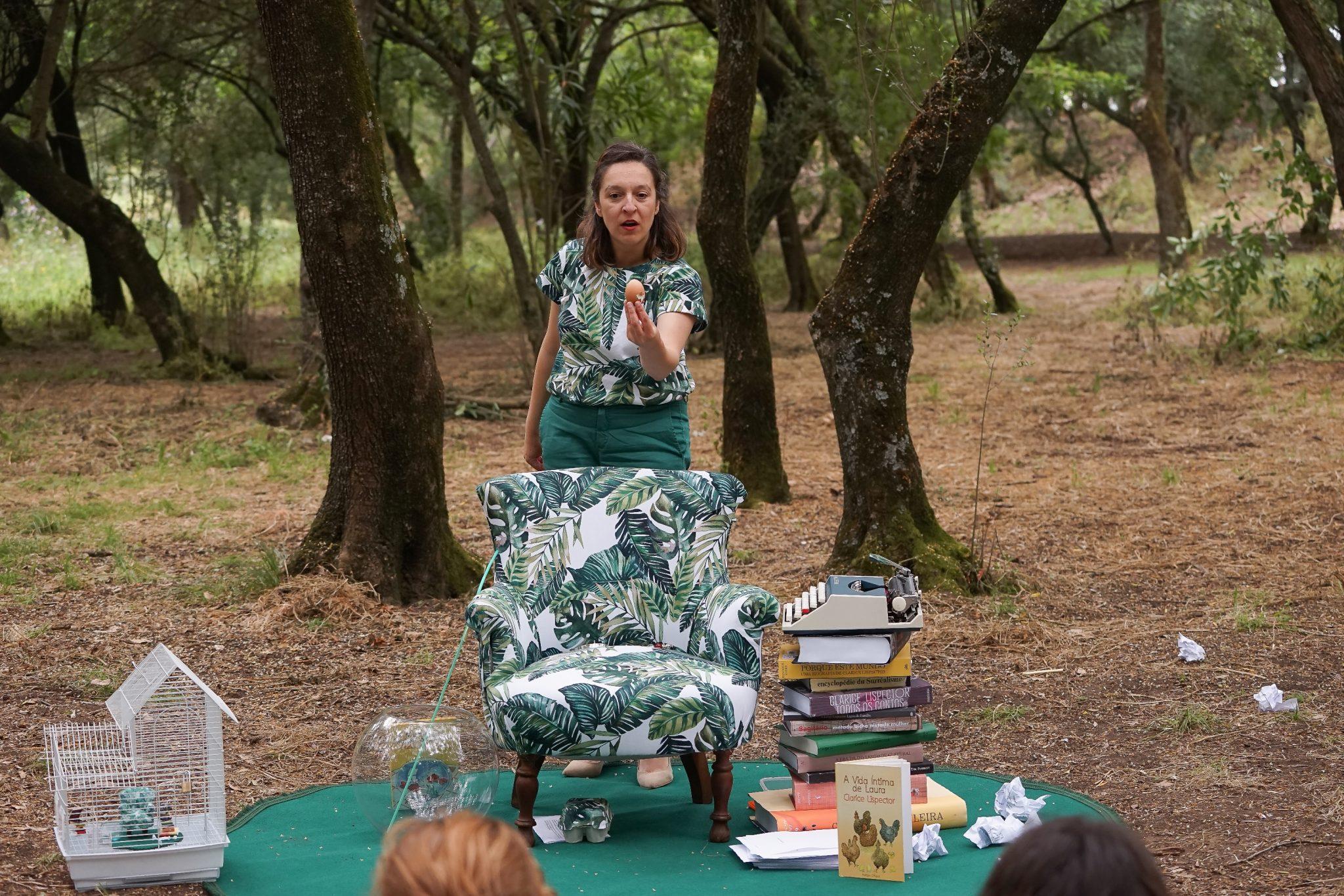 Mulher vestida de verde num parque rodeado de árvores segura um ovo e mostra-o de frente para o observador. À sua frente tem uma poltrona com um padrão de folhas verdes, uma gaiola branca e uma pilha de livros com uma máquina de escrever no topo.