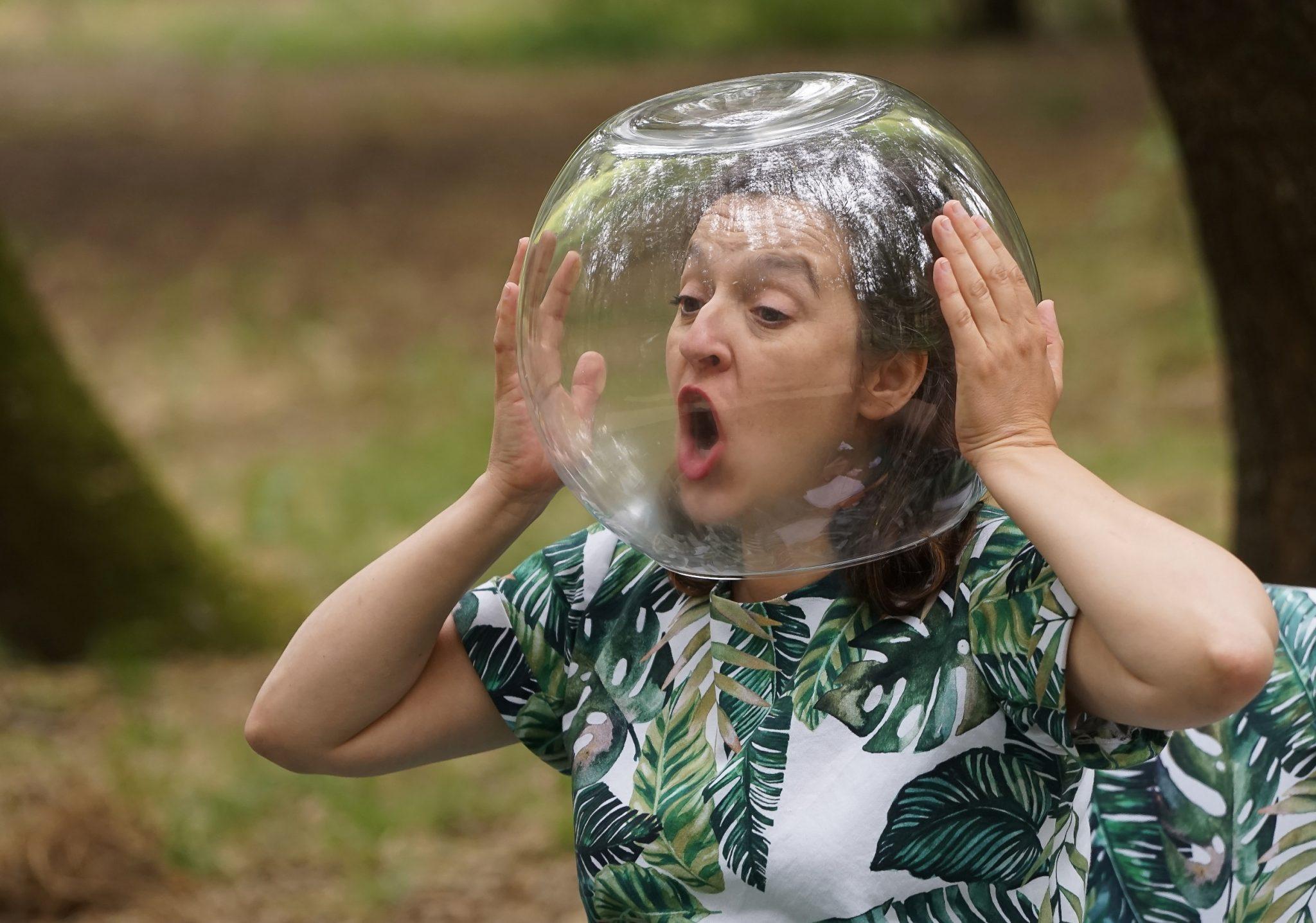 Mulher de boca aberta com a cabeça dentro de um aquário de peixes redondo. Está a olhar para o lado esquerdo do observador vestida com uma camisa com um padrão de folhas verdes
