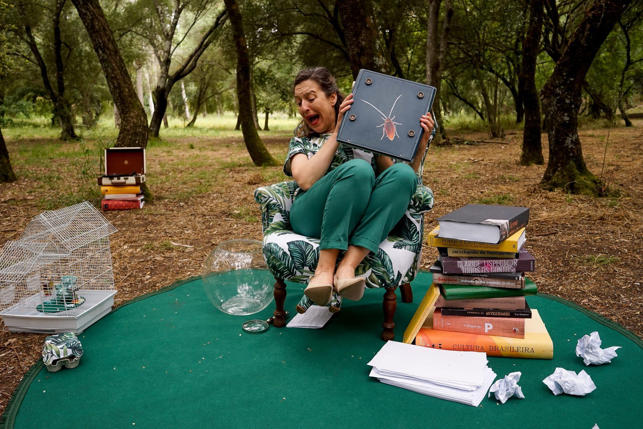 Mulher sentada numa cadeira, num jardim, com pernas levantadas a gritar assustada. A cadeira está por cima de um tapete verde e tem, do lado direito do observador, uma pilha de livros, e, do lado esquerdo, um aquário vazio