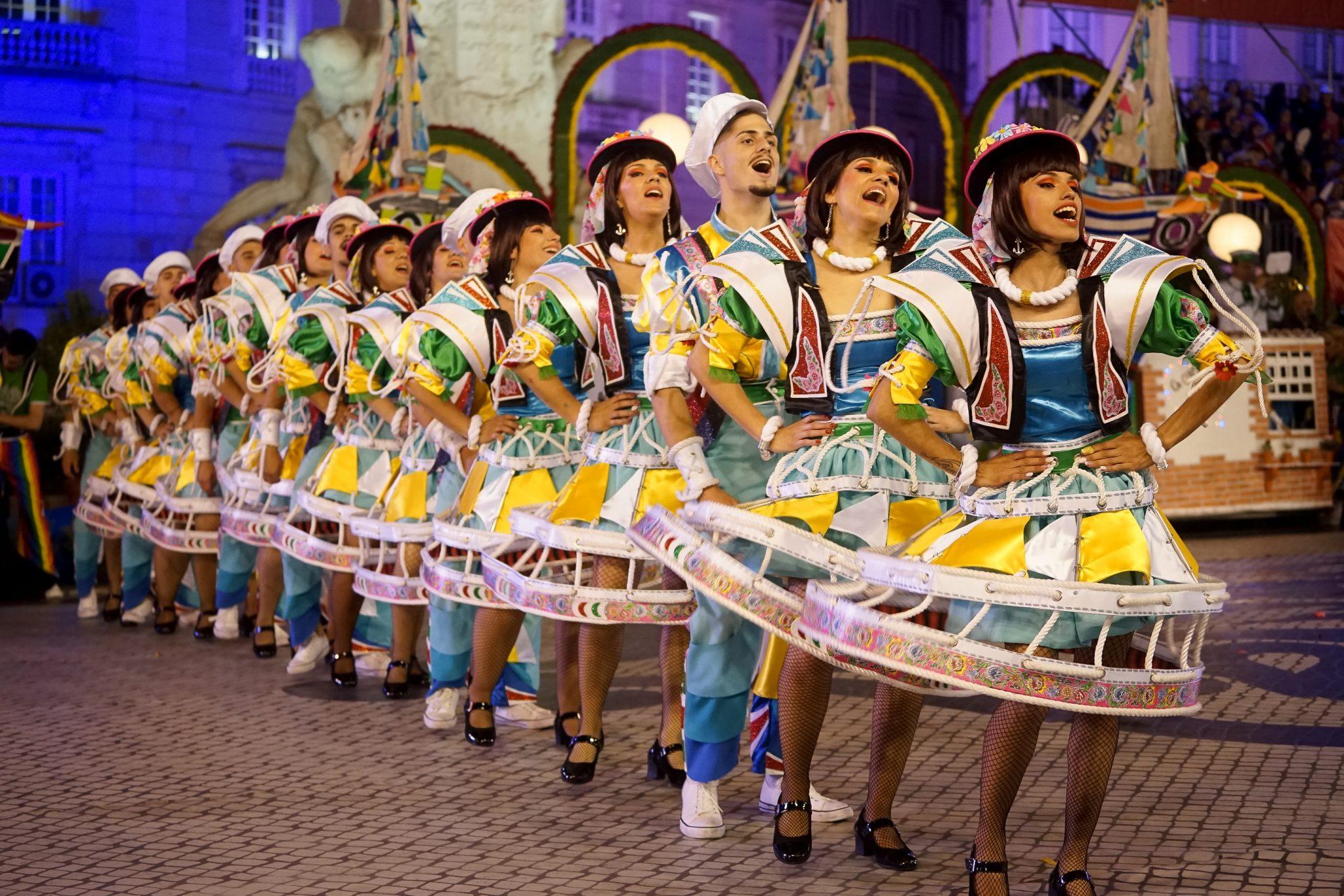 Uma fila composta por homens e mulheres a dançar e a cantar na Avenida da Liberdade. As mulheres têm um colete e uma saia larga feita de cordas torcidas de pesca e triângulos de tecido amarelos e brancos.