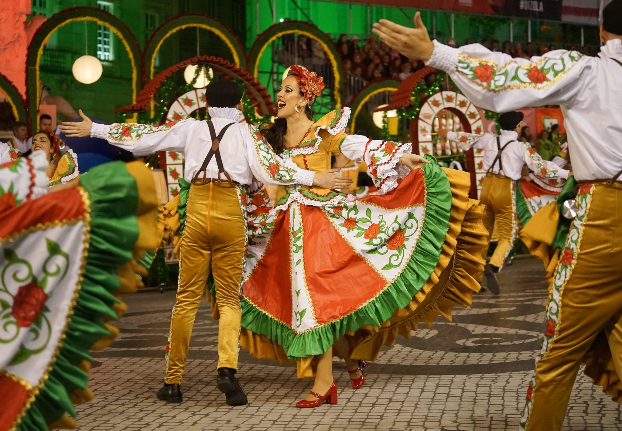 Um par de marchantes, homem e mulher, vestidos com roupas amarelas, brancas, vermelhas e verdes, dançam e rodam lado a lado