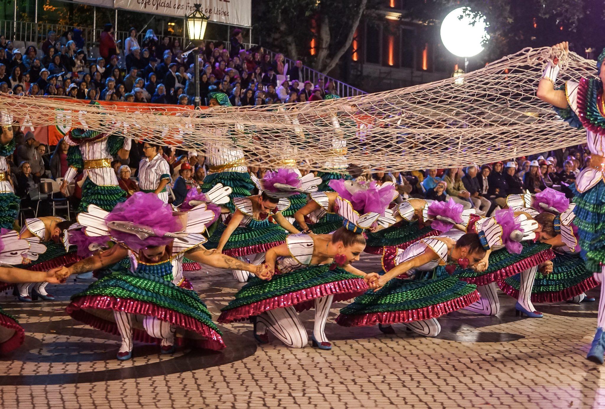 Sob uma rede de pesca de grandes dimensões, várias mulheres vestidas em tons de rosa e verde agacham-se. Em segundo plano, uma bancada com espetadores.