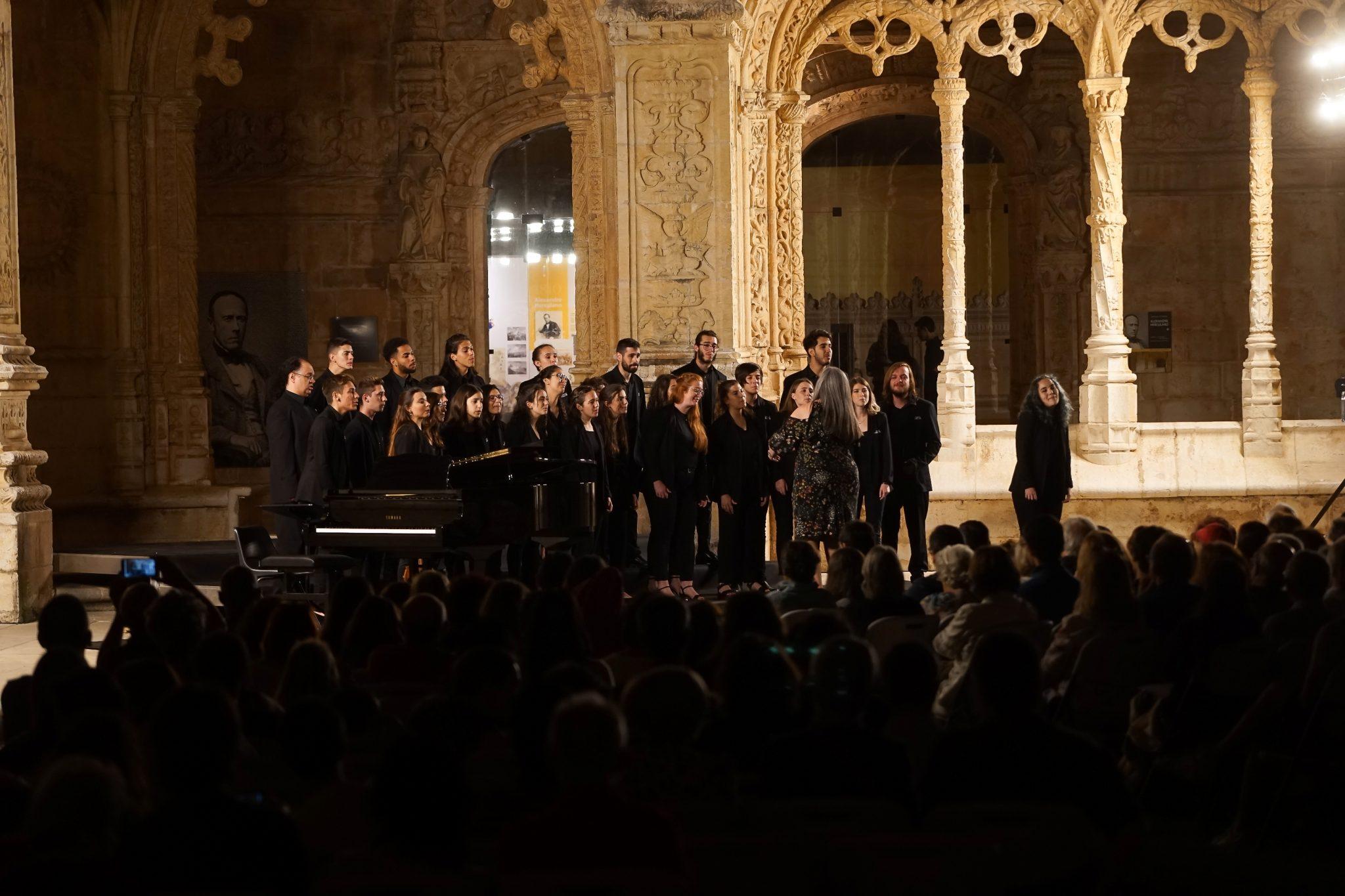 Grupo de cantores de coro vestidos de negro atuam no Claustro do Mosteiro dos Jerónimos à noite.