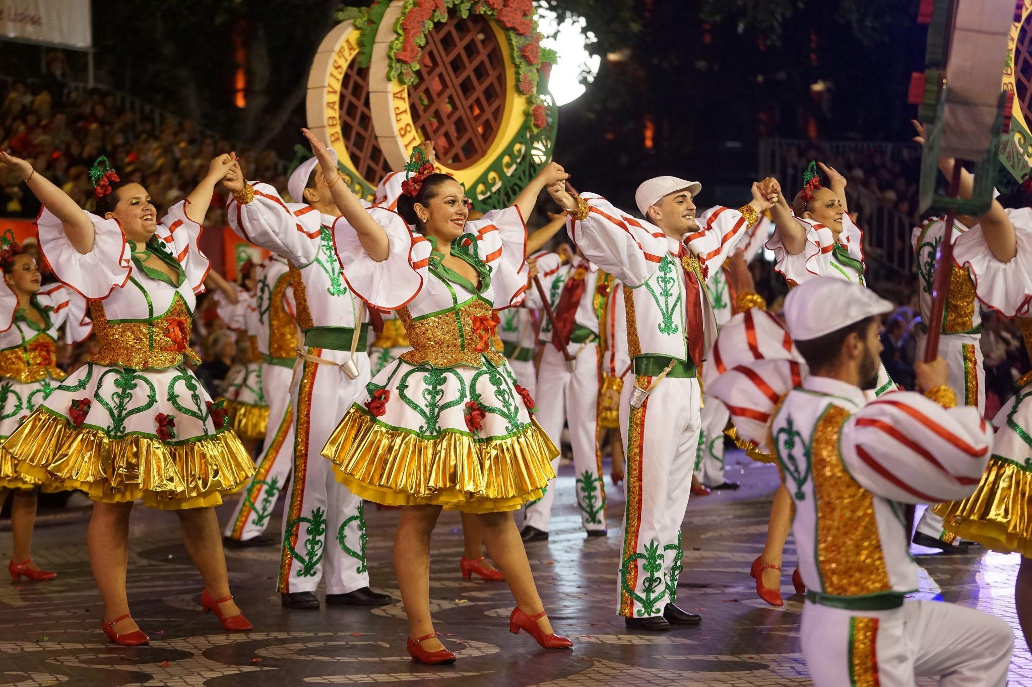De lado para o observador, um grupo de marchantes homens e mulheres sorriem para a frente de braços no ar e mãos dadas. Têm roupas brancas com pormenores verdes e dourados e flores vermelhas. Em segundo plano podem ver-se alguns arcos onde se lê Boavista.
