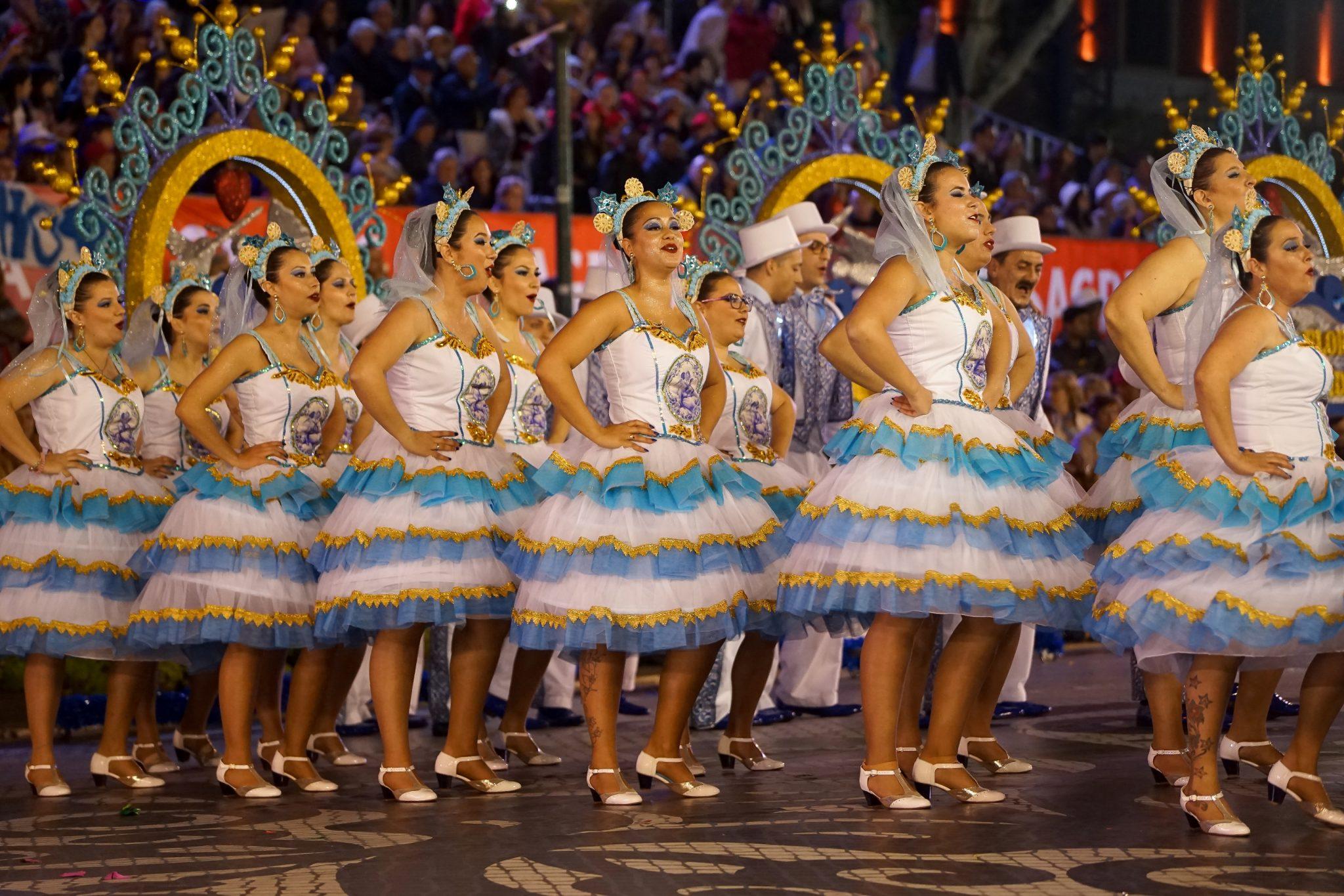De lado para o observador, uma fila de mulheres vestidas com roupa branca e azul marcha na Avenida da Liberdade. Em segundo plano há uma fila de homens e ainda os arcos em tons de dourado e azul.