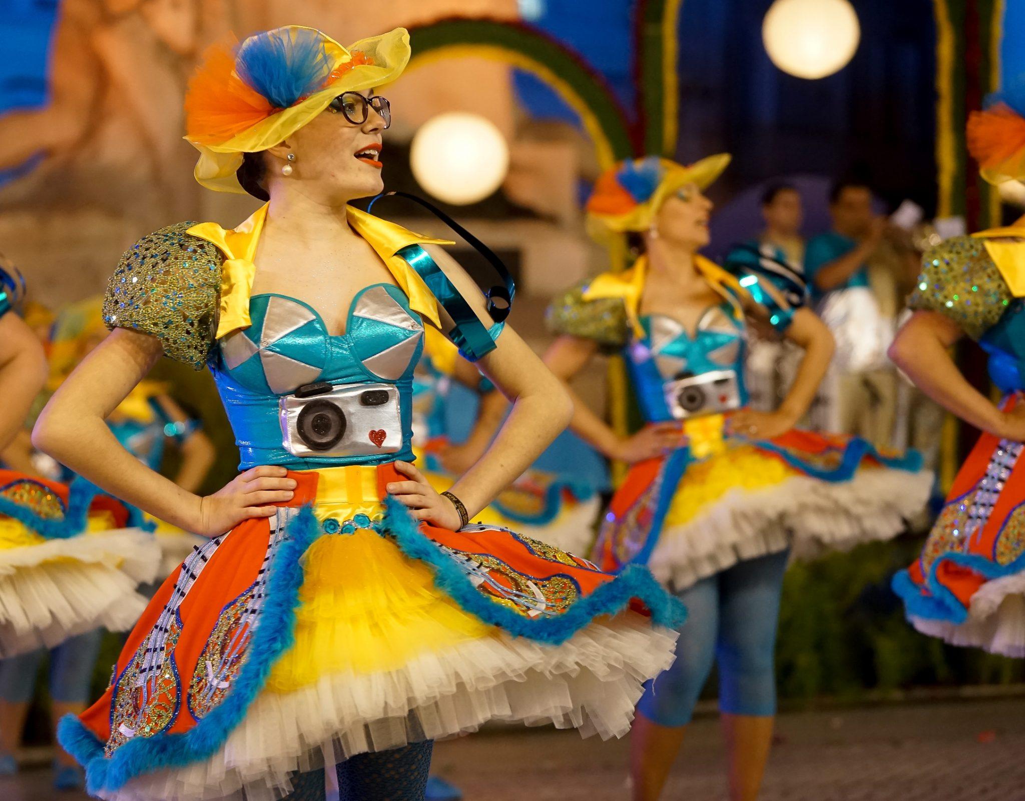 Em primeiro plano, uma mulher de corpete e saia colorida dança na Avenida da Liberdade.