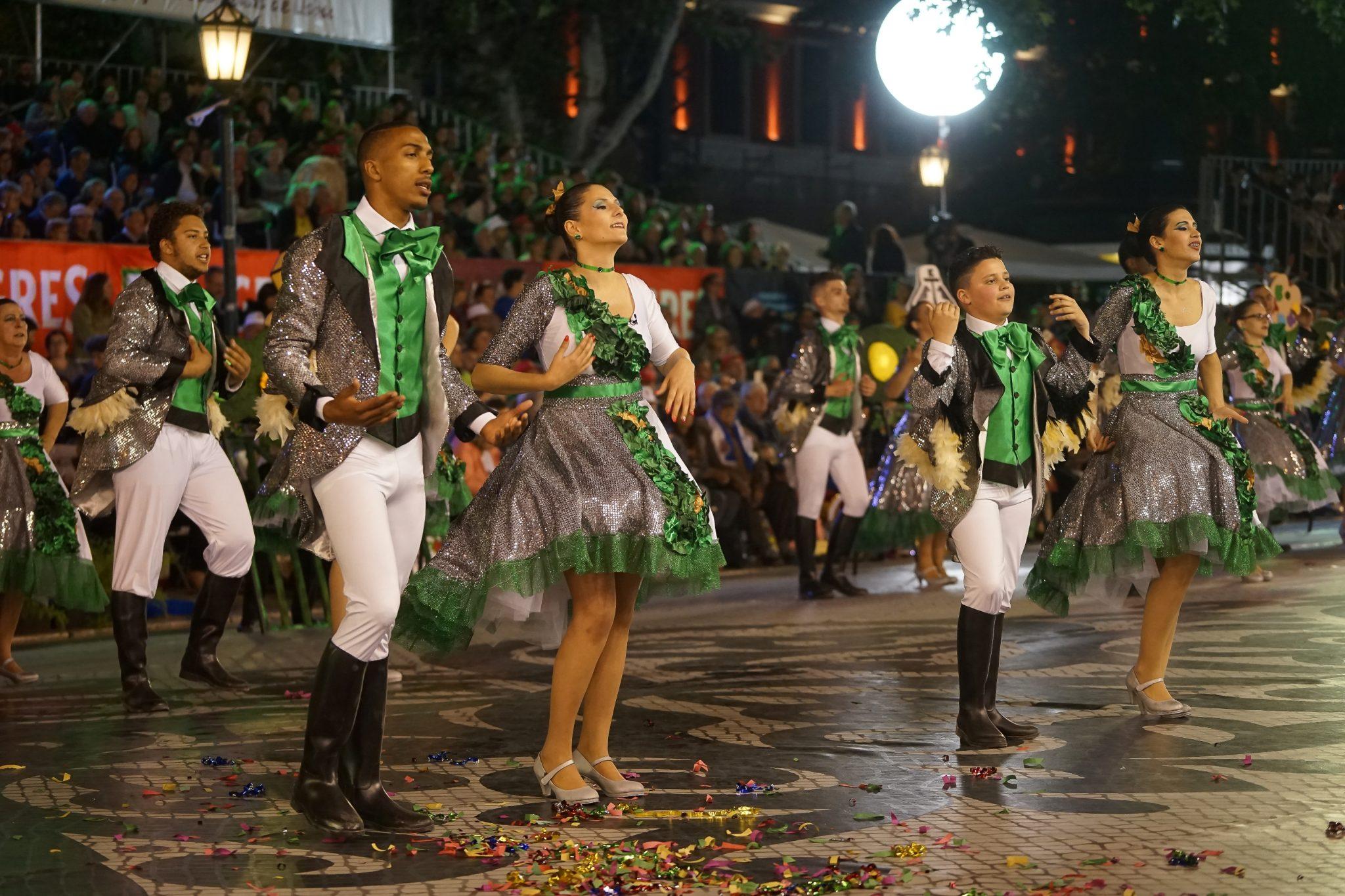 De lado para o observador, quatro marchantes (dois homens e duas mulheres) dançam na Avenida da Liberdade. Estão vestidos com roupas brancas, cinzentas e verdes.