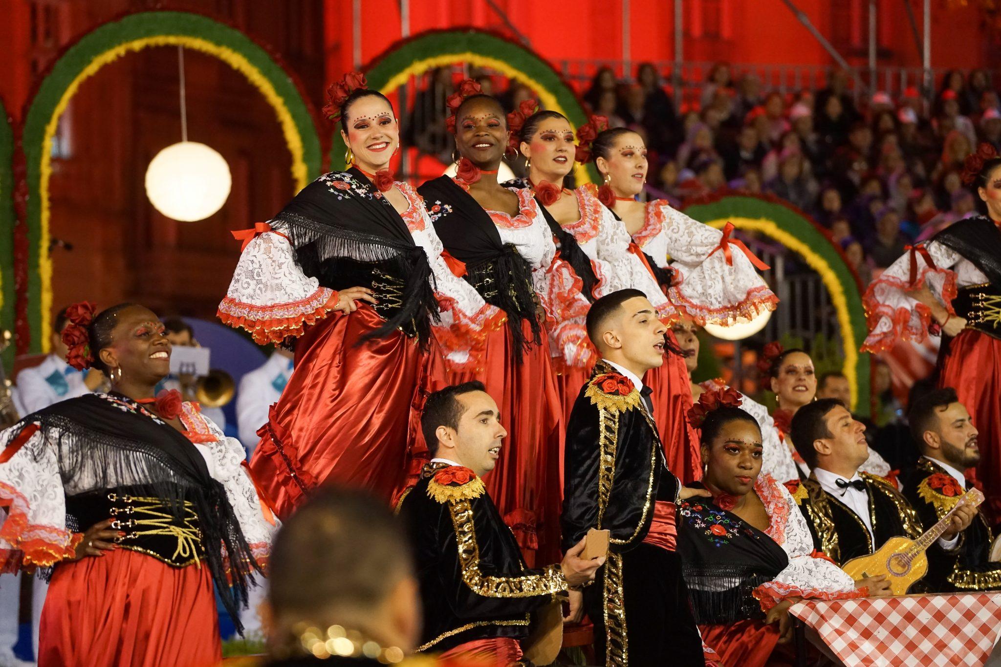 Quatro mulheres num plano elevado, de saia vermelha, blusa aos folhos branca e um xaile preto, sorriem para a frente do observador. Em seu redor, um grupo de marchantes homens e mulheres.