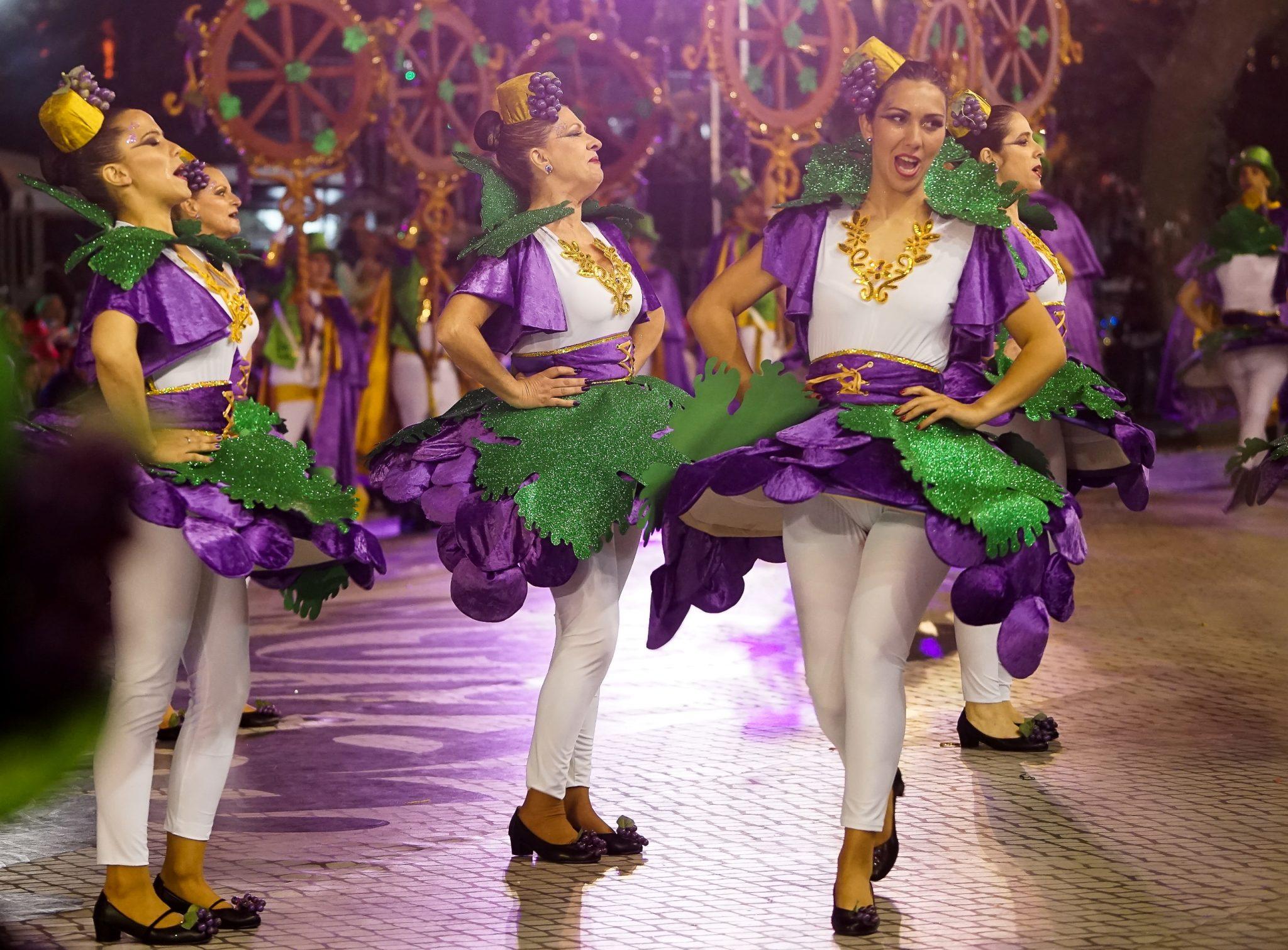 De frente para o observador, uma mulher canta e dança com roupa de cor branca, roxa e verde. Em segundo plano, de lado para o observador, três mulheres dançam.