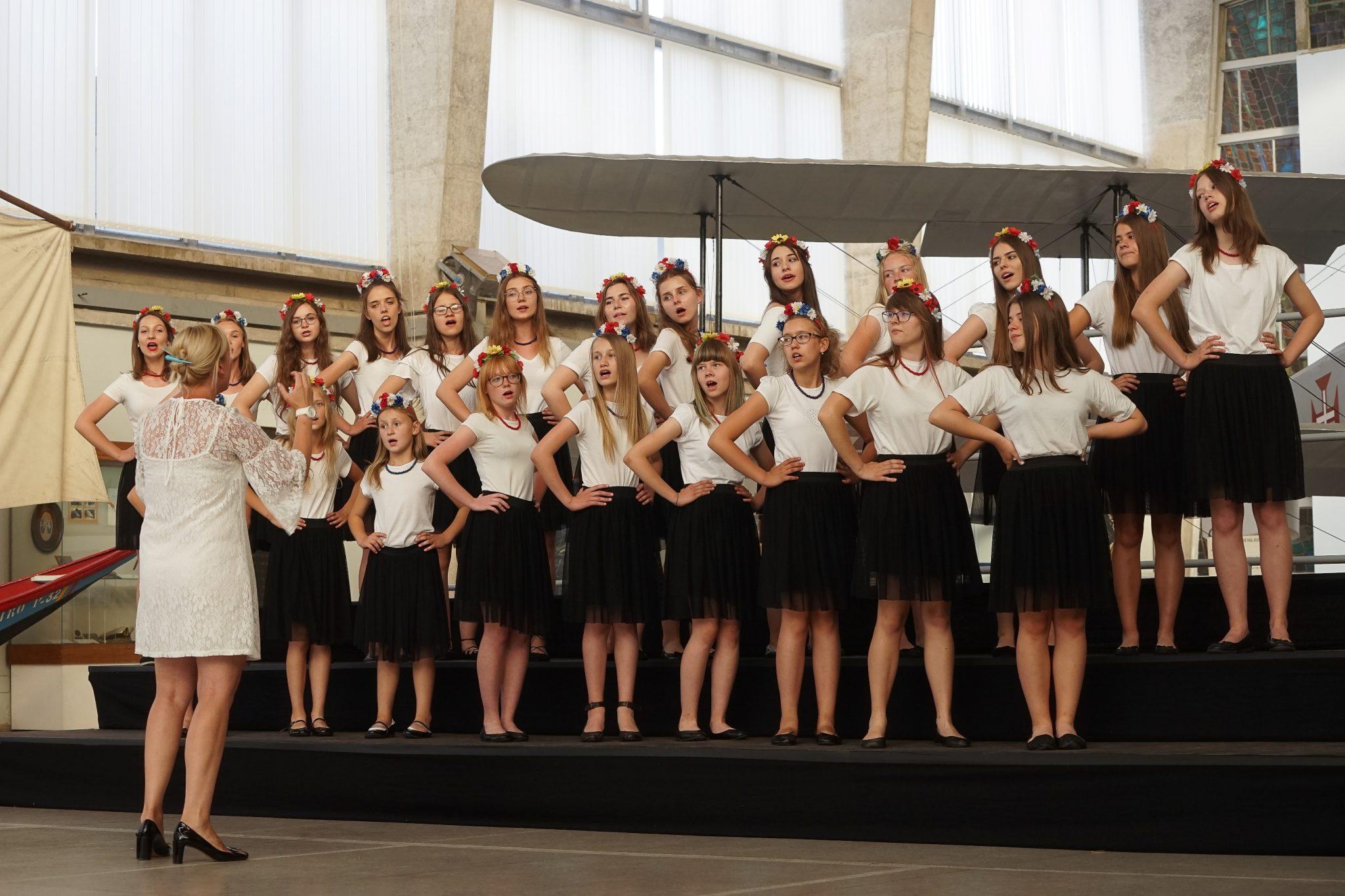 Jovens raparigas do coro polaco, vestidas de saia preta e t-shirt branca e com uma coroa de flores à cabeça, dançam de mãos na cintura durante a atuação no Museu da Marinha.