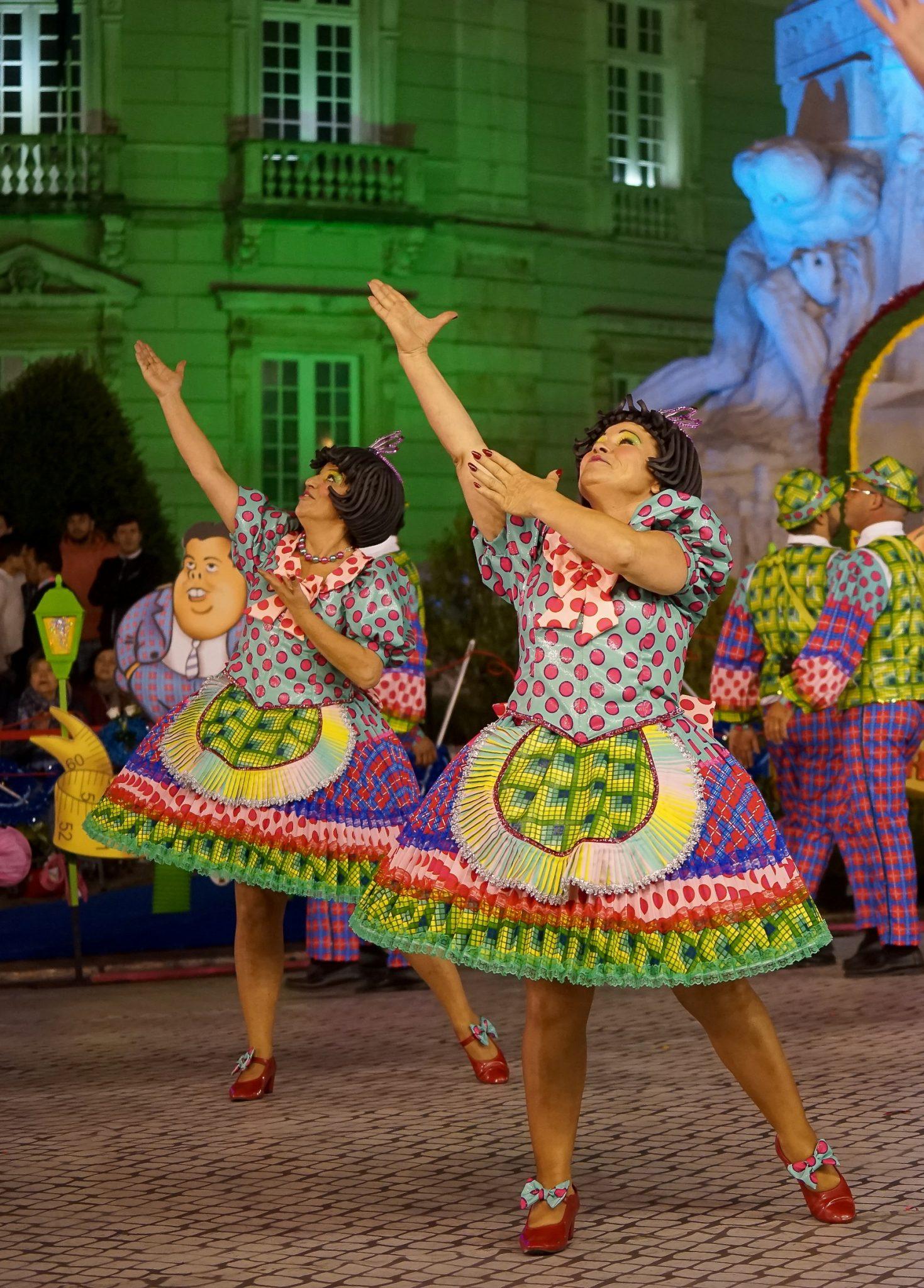 De frente para o observador, duas mulheres com vestidos coloridos, olham para cima enquanto elevam um dos braços na mesma direção e o outro permanece junto ao peito. Em segundo plano, marchantes masculinos e um arco pousado no chão com uma caricatura de Vasco Santana.