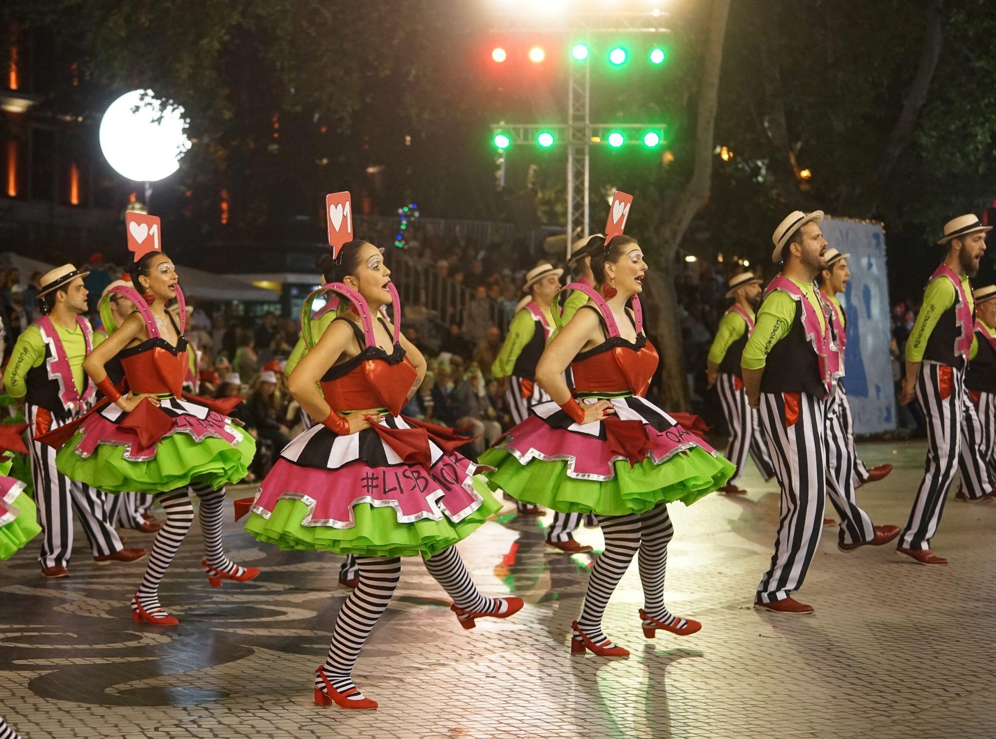 De lado para o observador, um grupo de marchantes (homens e mulheres) dança com uma perna no ar. As mulheres têm saias verde e rosa e as mãos na cintura. Os homens têm calças às riscas verticais pretas e brancas e as mãos atrás das costas.
