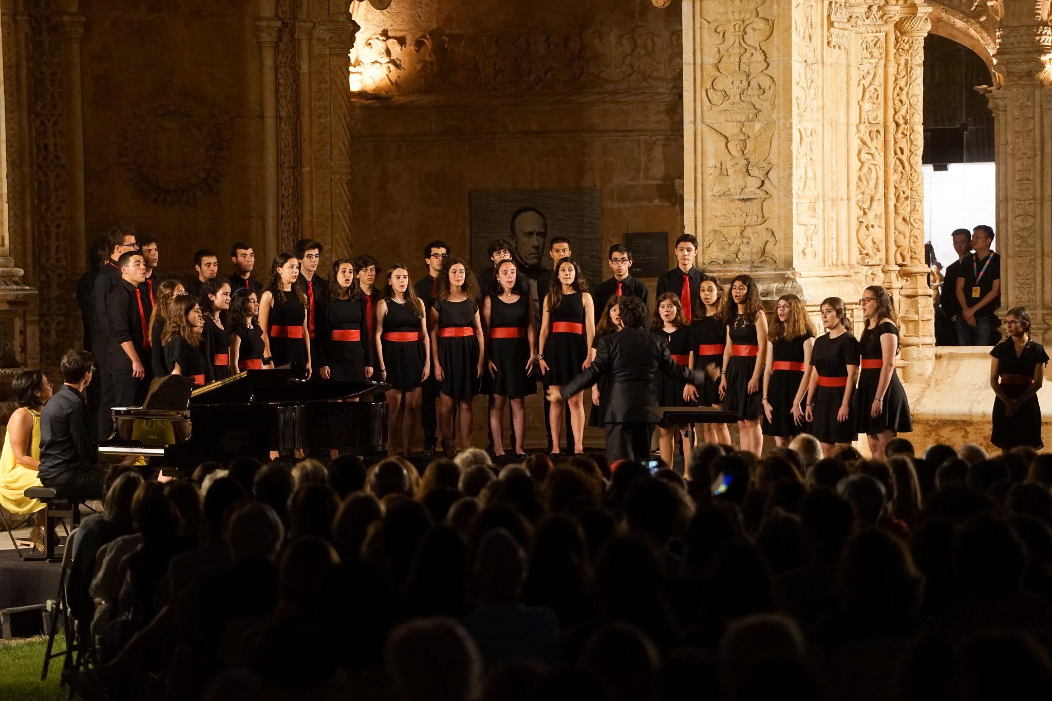 Jovens vestidos de negro com apontamentos vermelhos (no caso dos rapazes uma gravata, no caso das raparigas uma tira à cintura) cantam no Claustro do Mosteiro dos Jerónimos à noite. À sua frente podem ver-se as cabeças dos espetadores