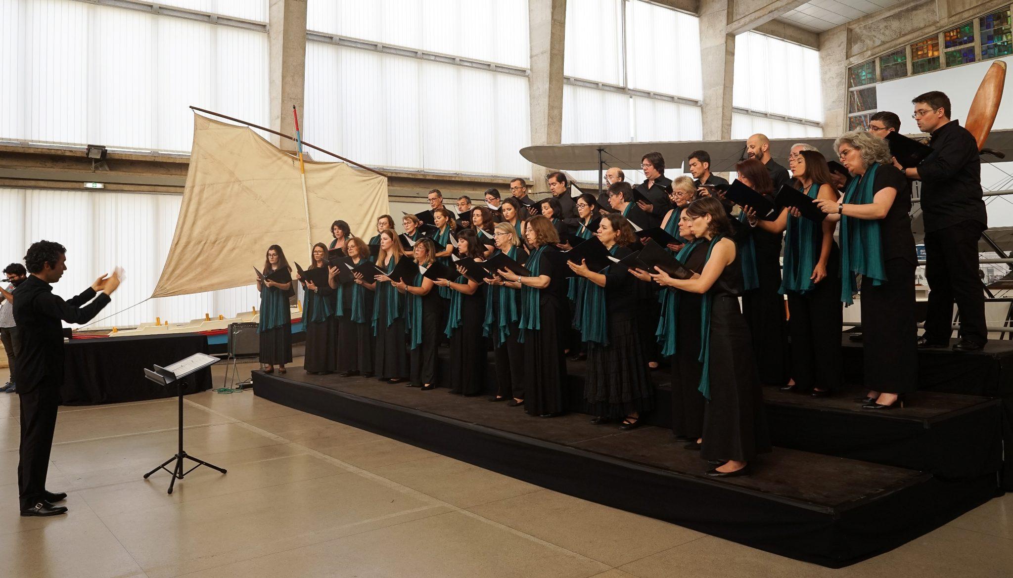 Homens e mulheres, ambos vestidos de negro - elas com um lenço verde ao pescoço -, cantam no Museu da Marinha e seguram as partituras nas mãos. À sua frente, o maestro dirige a atuação.