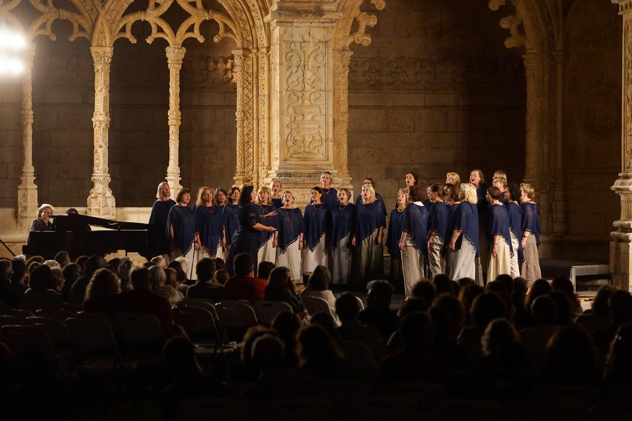 Coro composto por várias mulheres, vestidas com roupas cremes e um poncho azul escuro, cantam à noite no Claustro do Mosteiro dos Jerónimos. À esquerda, uma mulher toca piano. À frente são visíveis silhuetas de espetadores.