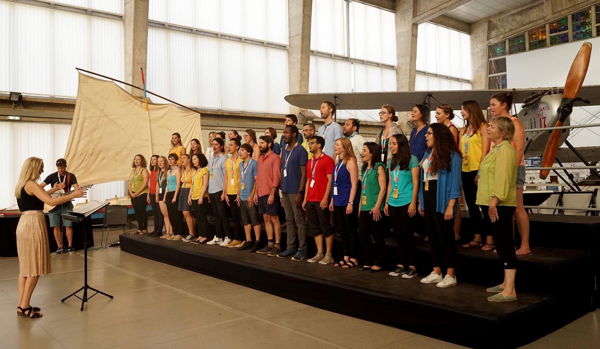 Homens e mulheres com camisas coloridas cantam em pé num estrado com três patamares. Atrás deles, encontra-se um avião de modelo antigo.