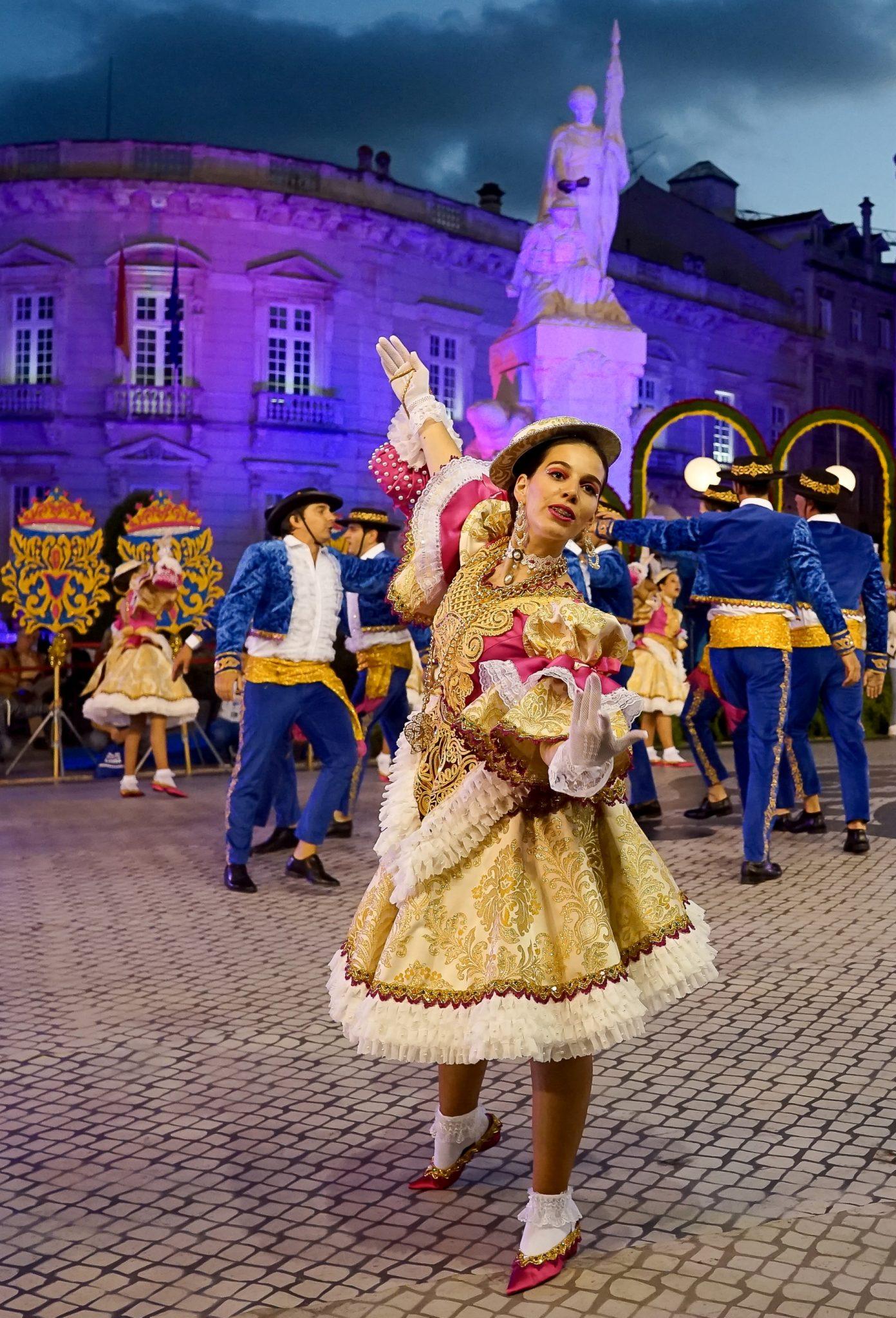 Uma mulher de vestido dourado com folhos brancos dança. Atrás dela um grupo de homens de roupa azul dança numa roda. Em segundo plano, uma estátua composta por uma figura masculina e uma feminina.