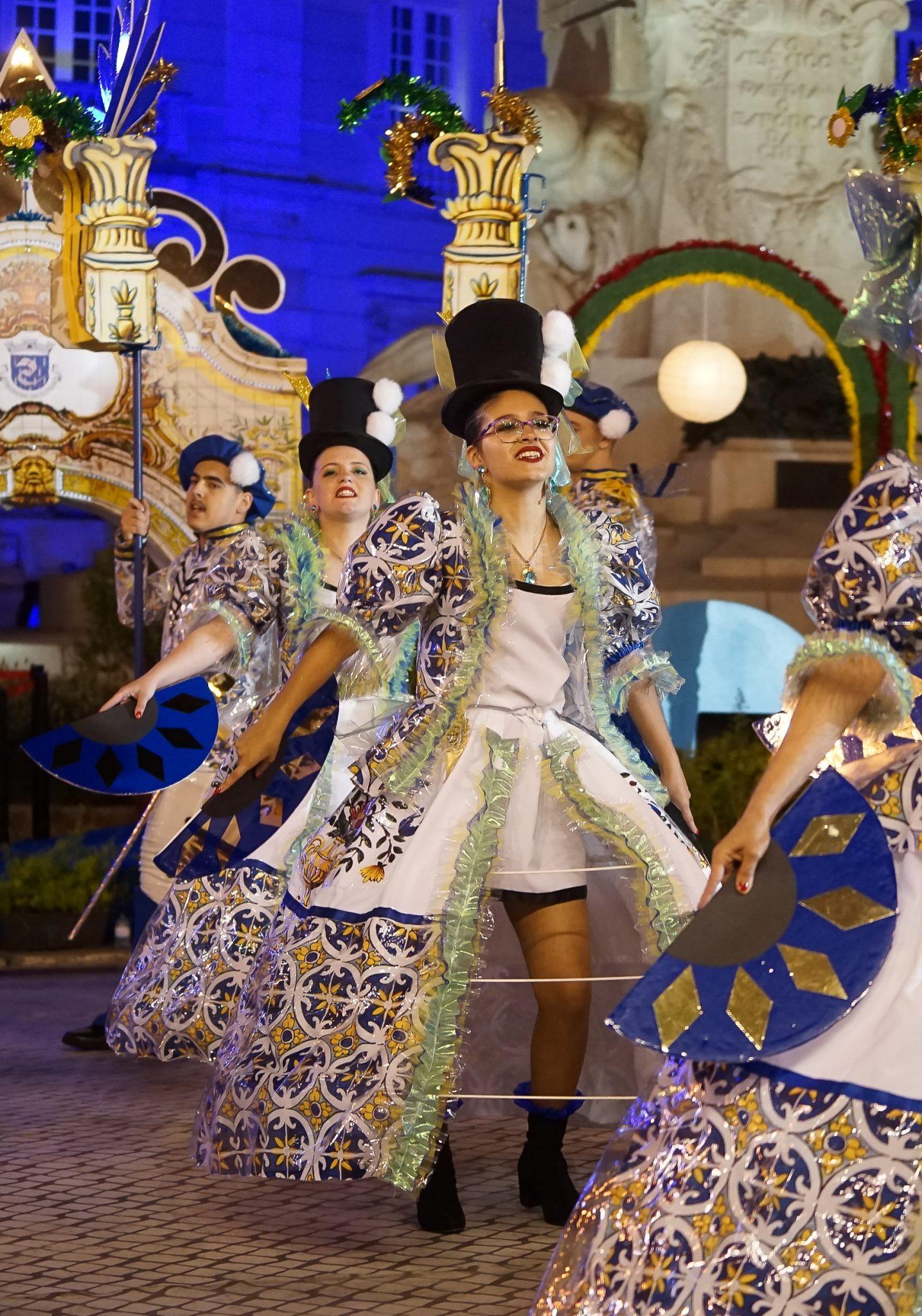 Em primeiro plano, uma mulher com uma saia larga e um casaco com um padrão de azulejos azuis, brancos e amarelos, e uma cartola preta. Em segundo plano, outros marchantes e os arcos que procuram figurar fontes e chafarizes.